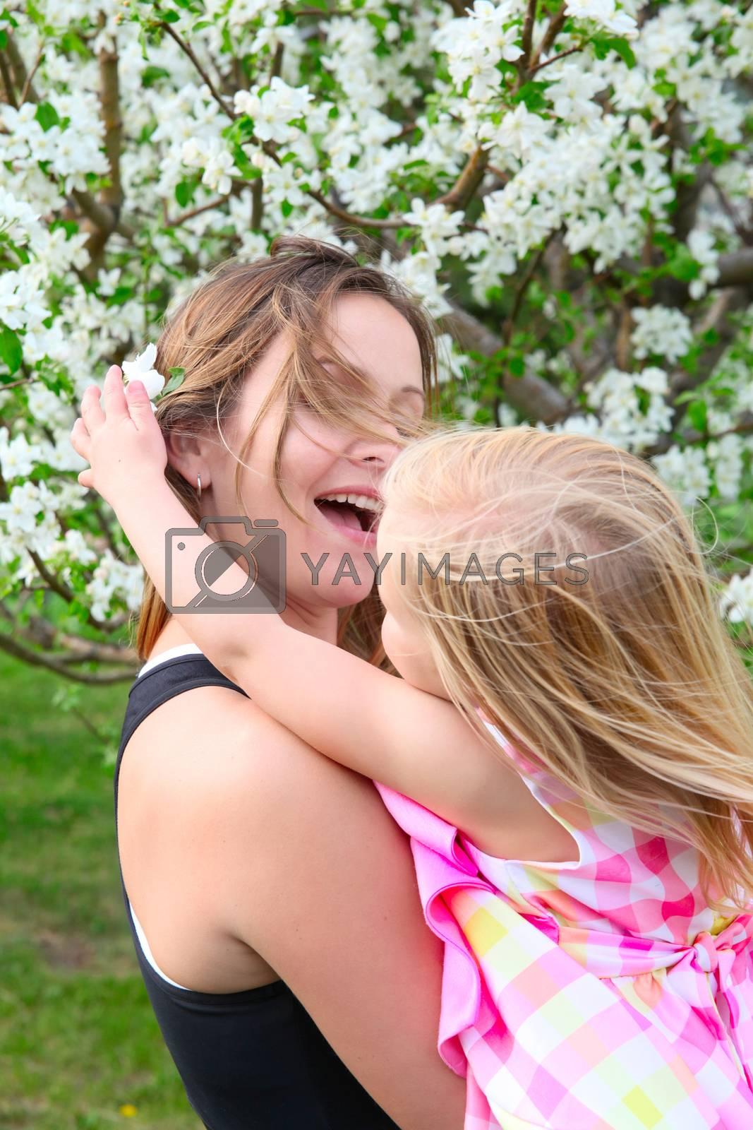 Little blond girld and her mom in a spring blossom garden