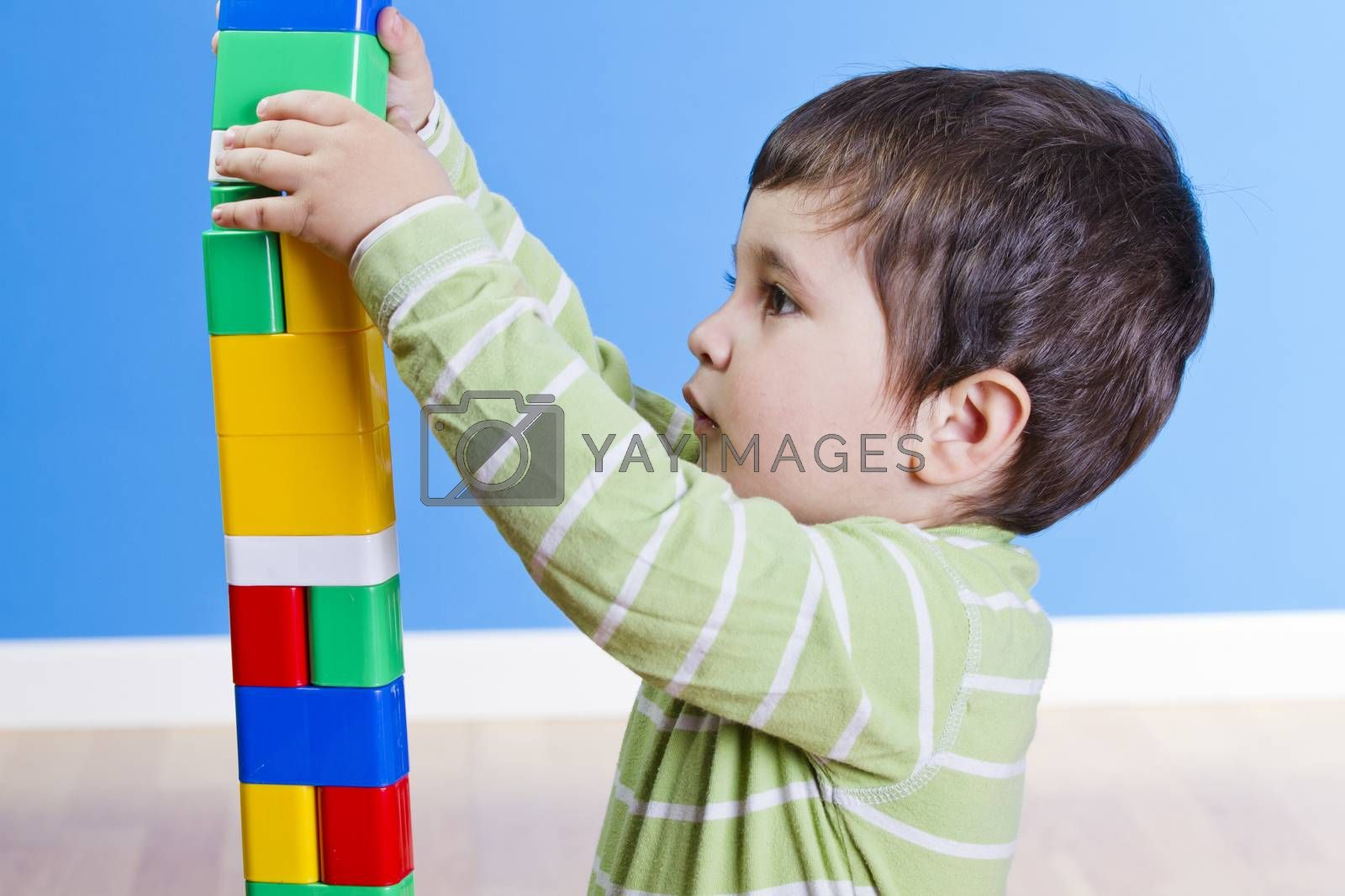 Cute little child is playing with toys while sitting on floor