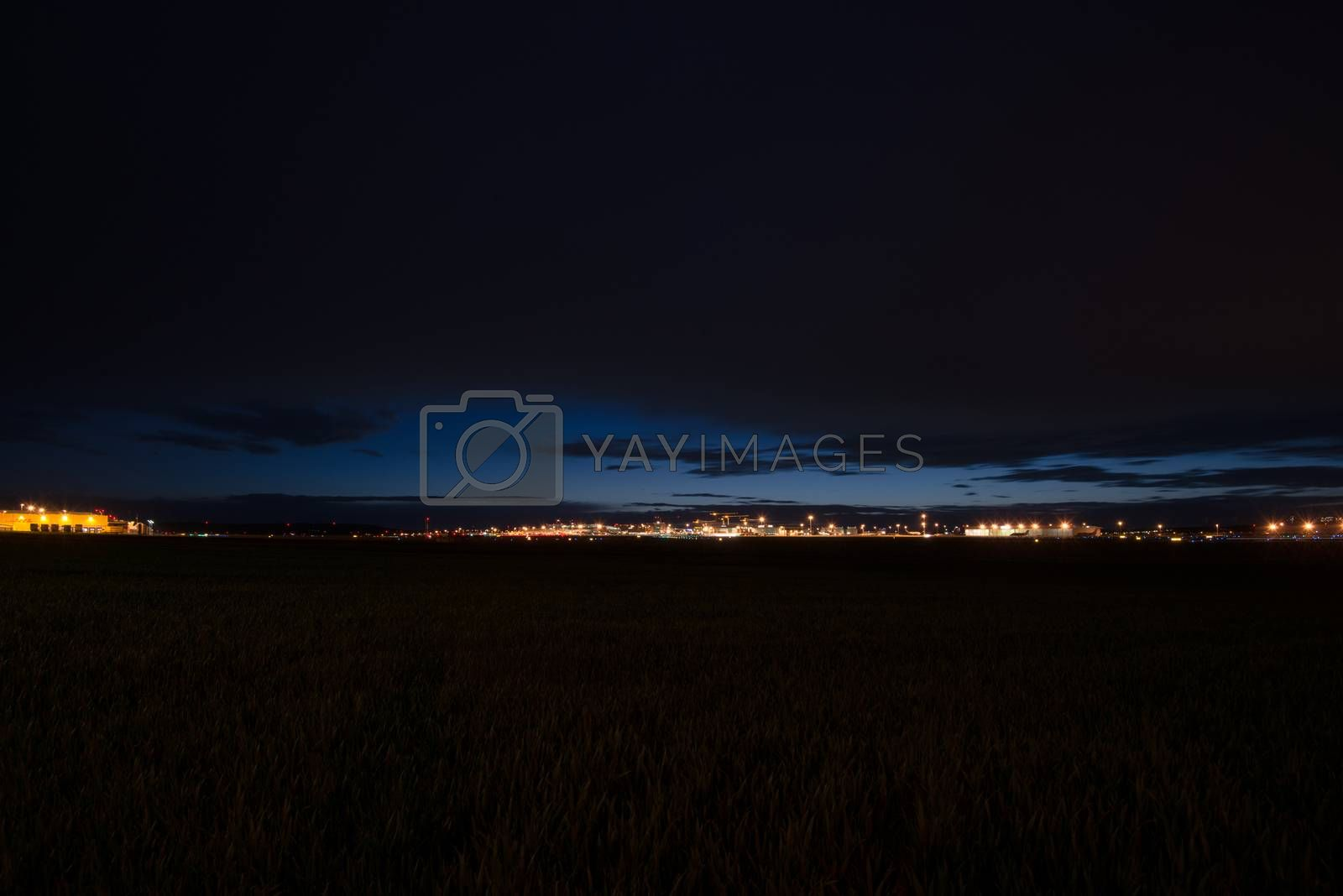 STUTTGART, GERMANY - MAY 6, 2014: Extreme wide angle shot of Stuttgart Airport at dusk with planes departing and arriving as seen from over the fields on May, 6, 2014 in Stuttgart, Germany. Stuttgart Airport is the 6th biggest airport in Germany, having a capacity of 14 million people per year.