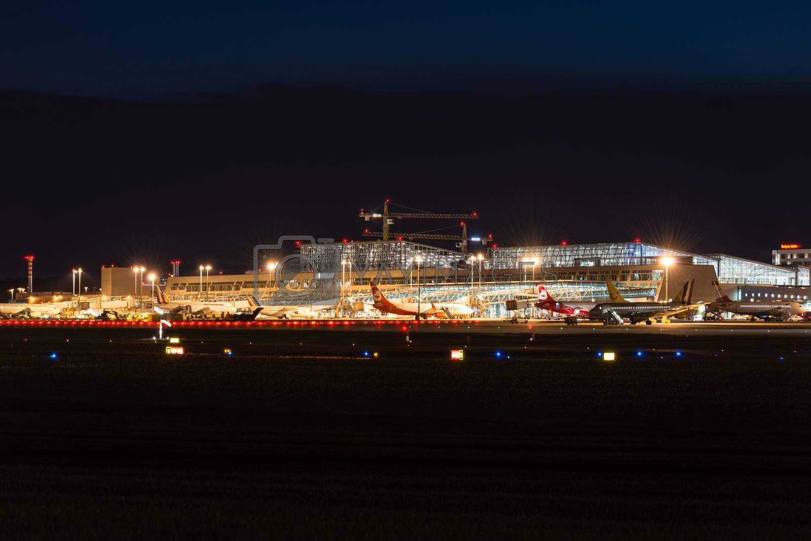 STUTTGART, GERMANY - MAY 6, 2014: Stuttgart Airport at dusk with planes departing and arriving as seen from over the fields on May, 6, 2014 in Stuttgart, Germany. Stuttgart Airport is the 6th biggest airport in Germany, having a capacity of 14 million people per year.