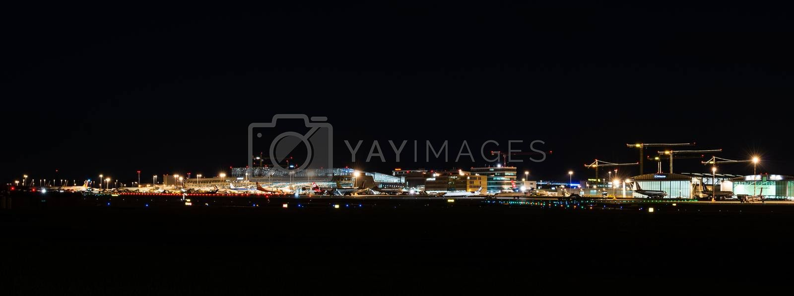 STUTTGART, GERMANY - MAY 6, 2014: Wide angle shot of Stuttgart Airport at dusk with planes departing and arriving as seen from over the fields on May, 6, 2014 in Stuttgart, Germany. Stuttgart Airport is the 6th biggest airport in Germany, having a capacity of 14 million people per year.