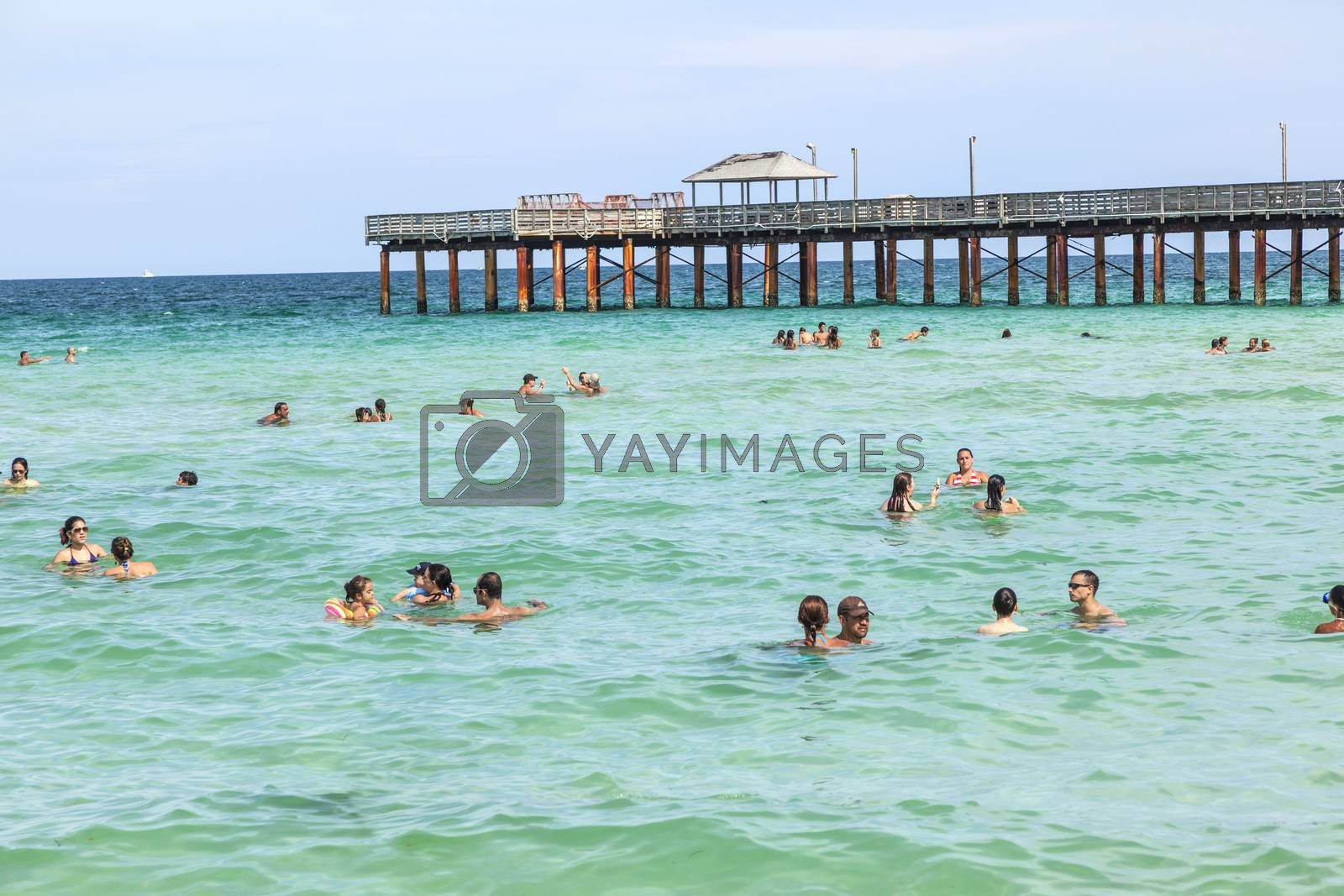 people enjoy swimming at  pier on a beach in Miami by meinzahn