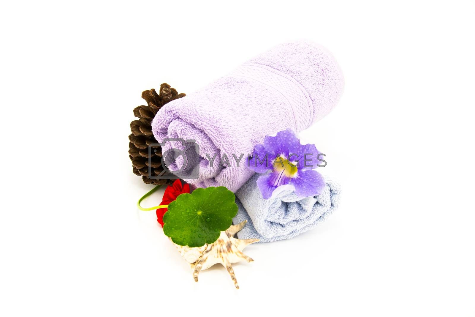 Spa and wellness setting with towels and flower.