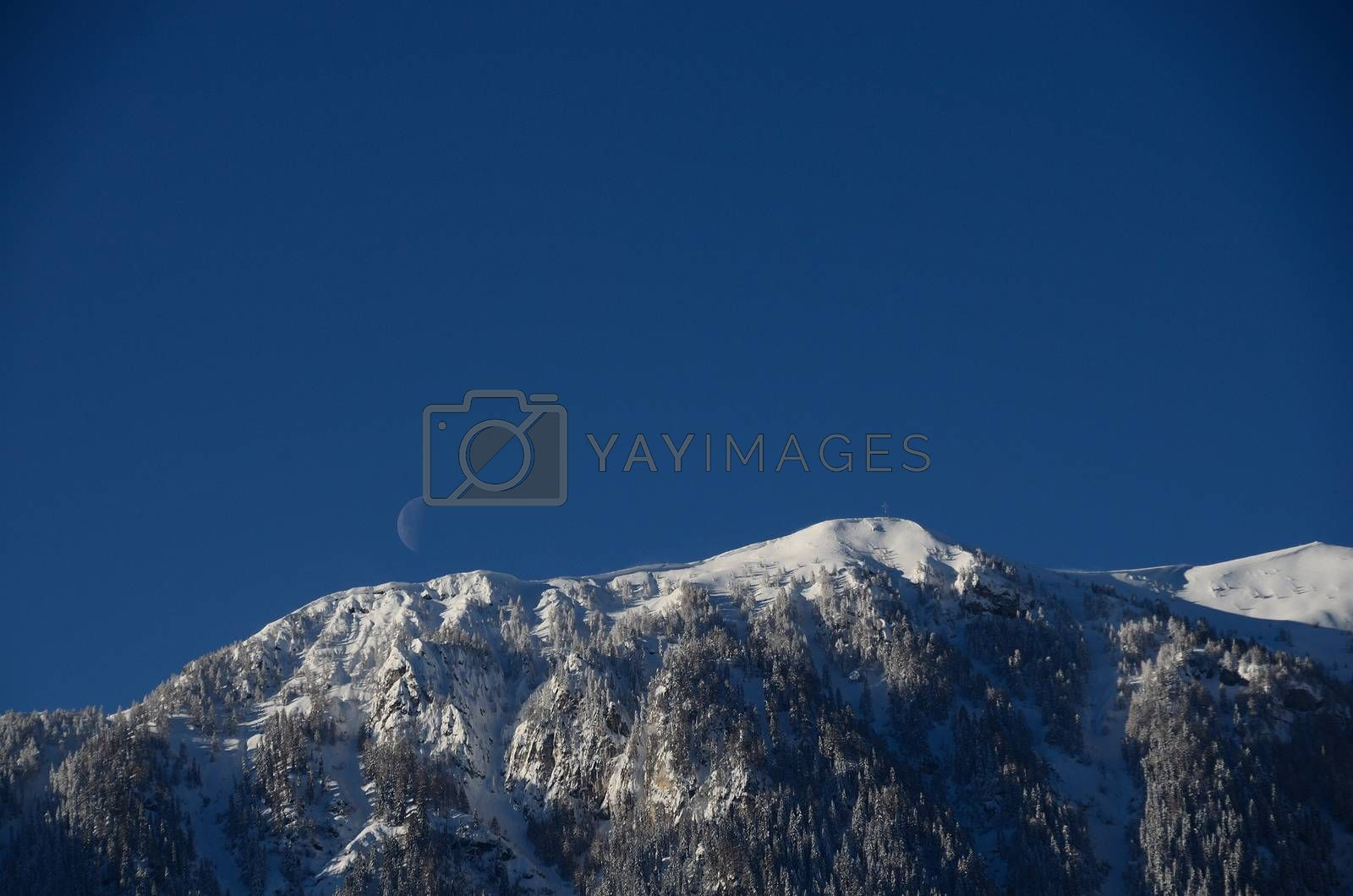 high mountain with snow and moon on blue sky