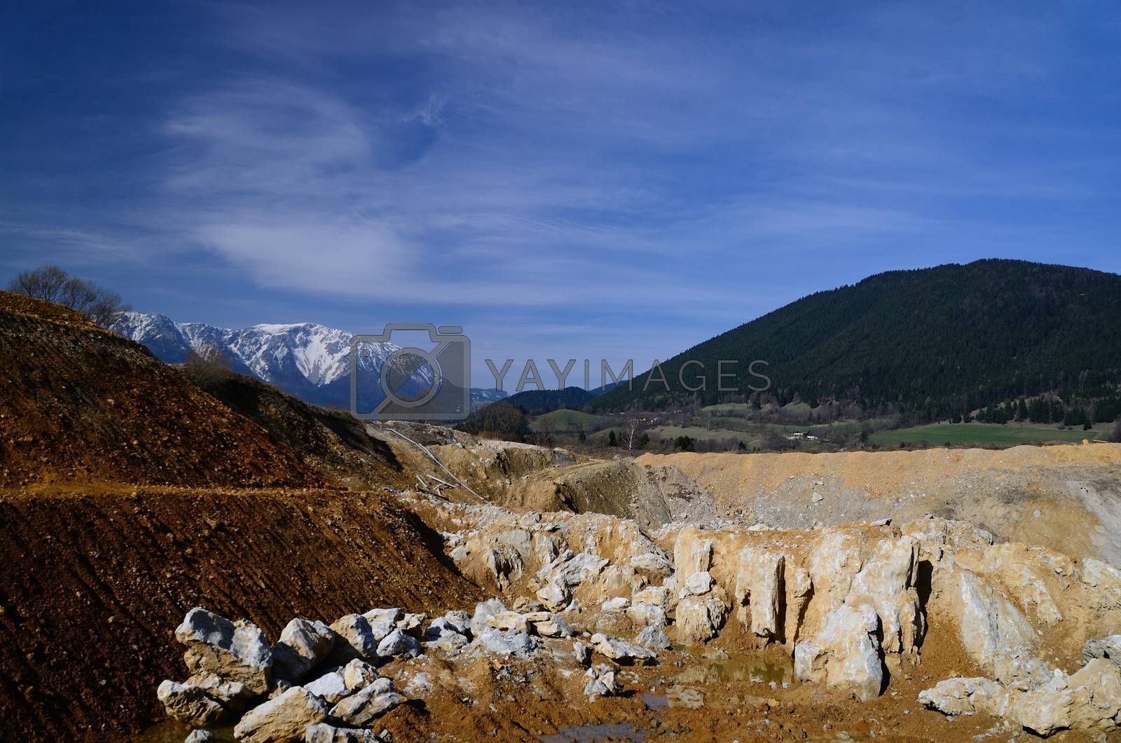 large deep quarry and snowy mountain in the background