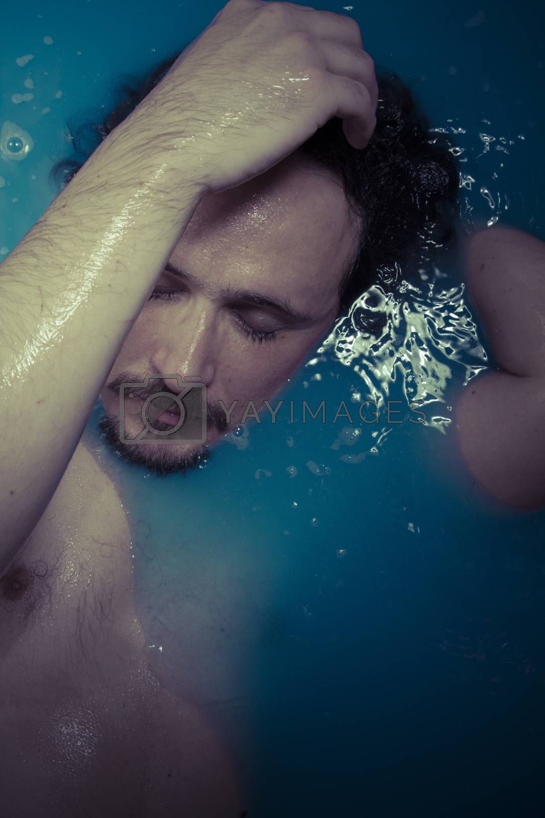 Depression, man in blue tub full of water, sadness concept by FernandoCortes