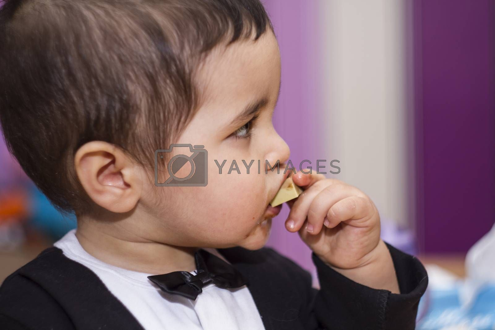 Adorable happy baby eating chocolate, wearing suit and bow tie by FernandoCortes