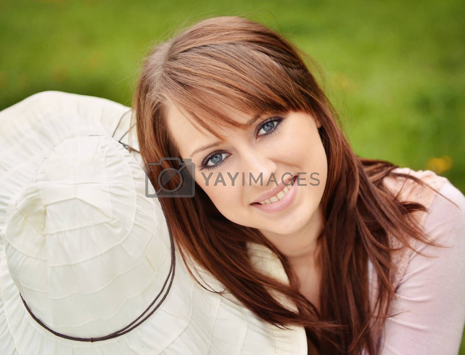 beautiful girl with sun hat over green grass background
