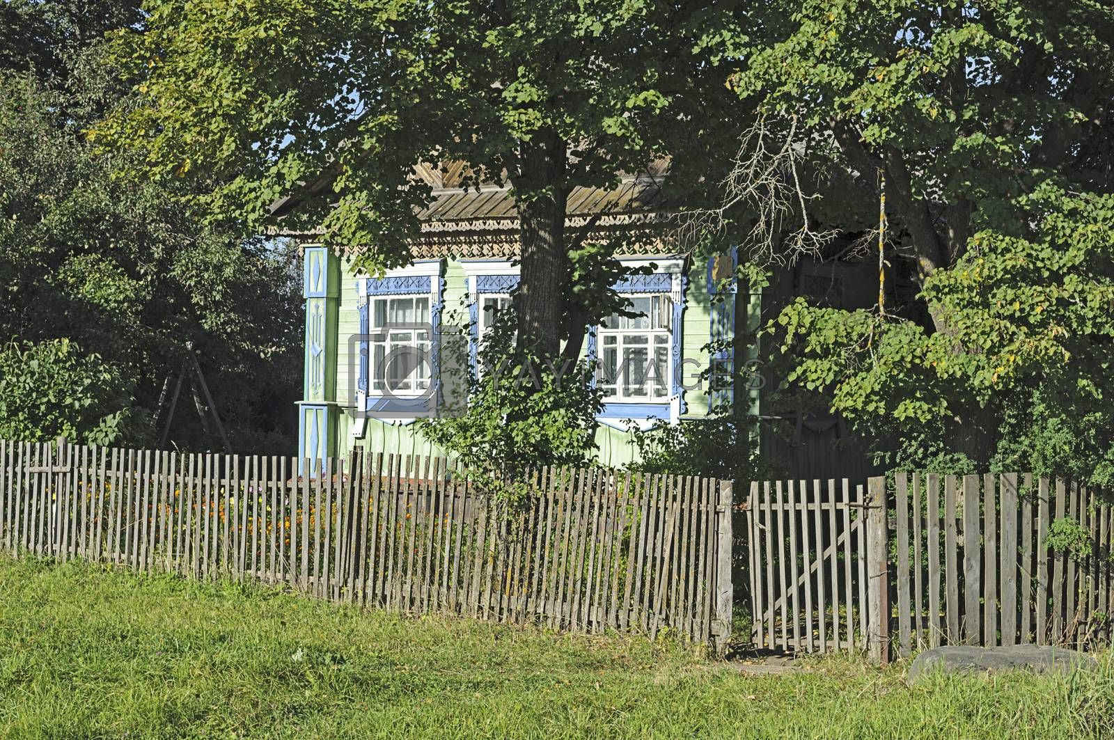 Small village house in shade of trees behind the old wooden fence