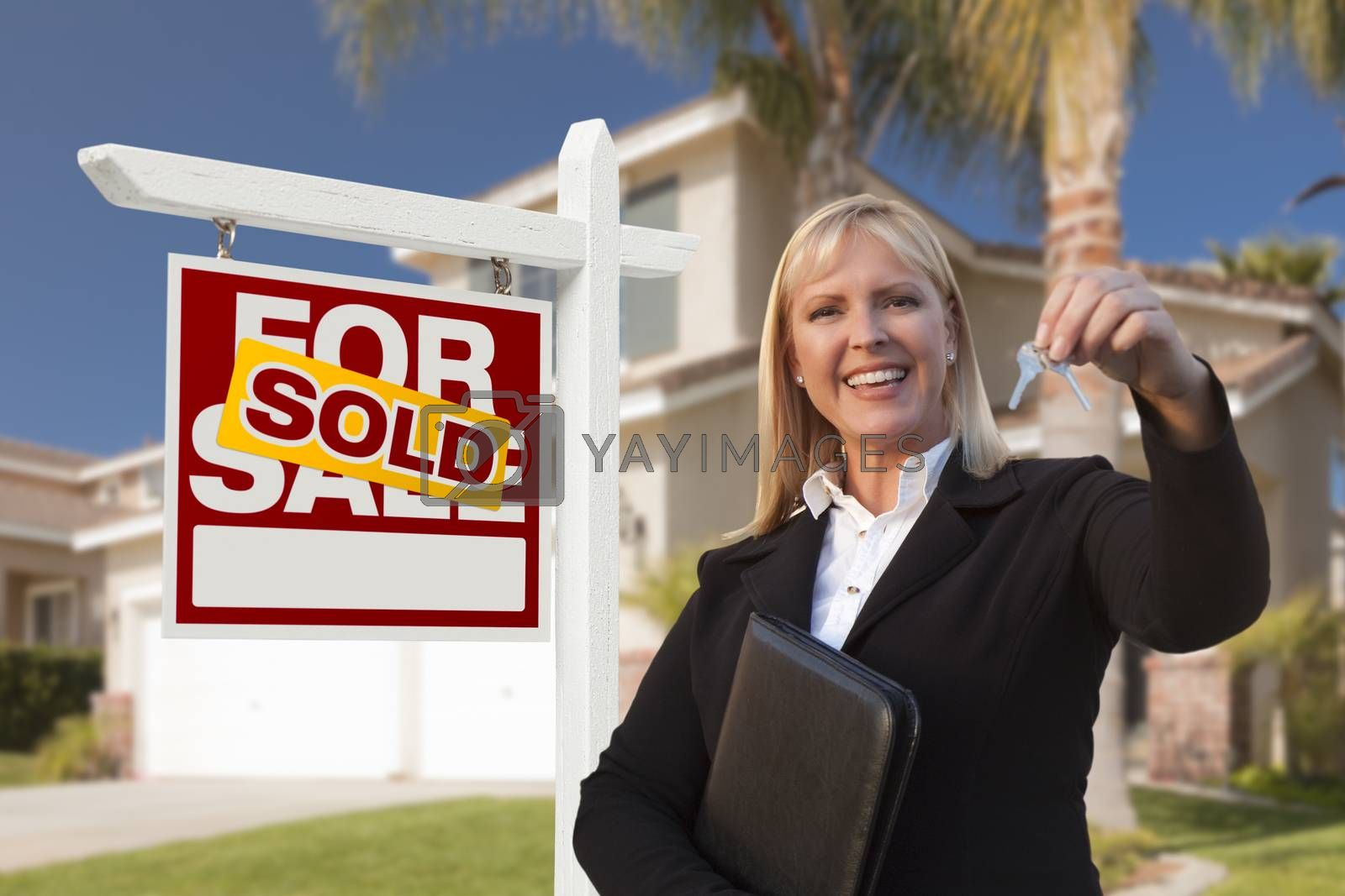 Royalty free image of Female Real Estate Agent Handing Over the House Keys by Feverpitched