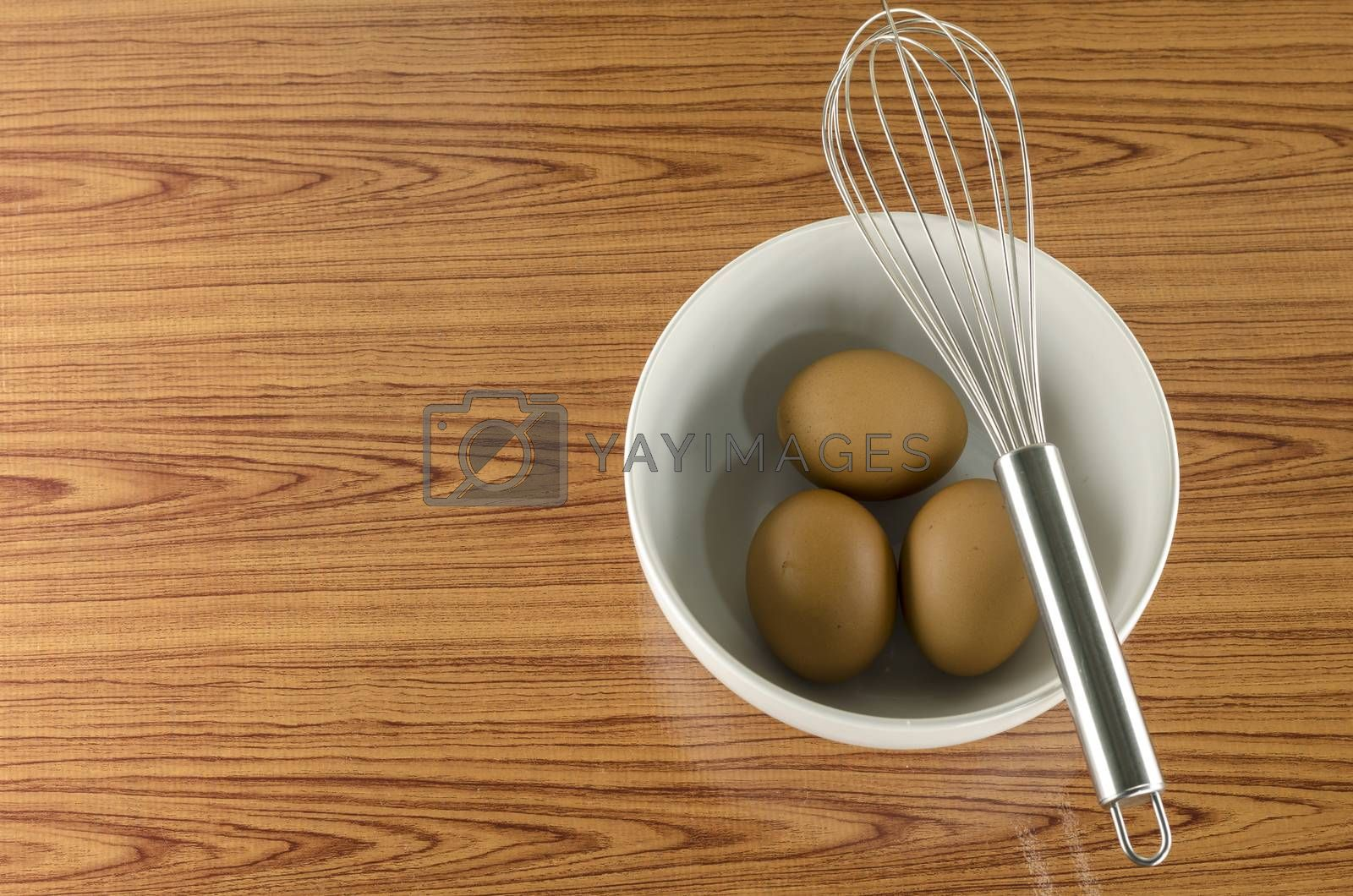 Royalty free image of whisk and egg in white bowl by ammza12