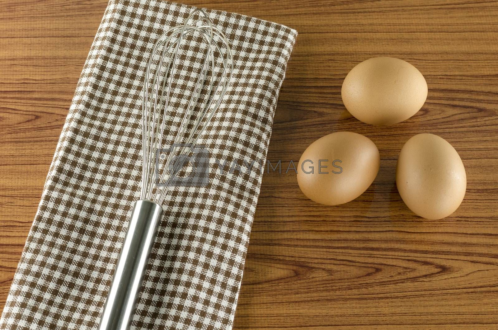 Royalty free image of whisk egg and brown kitchen towel by ammza12
