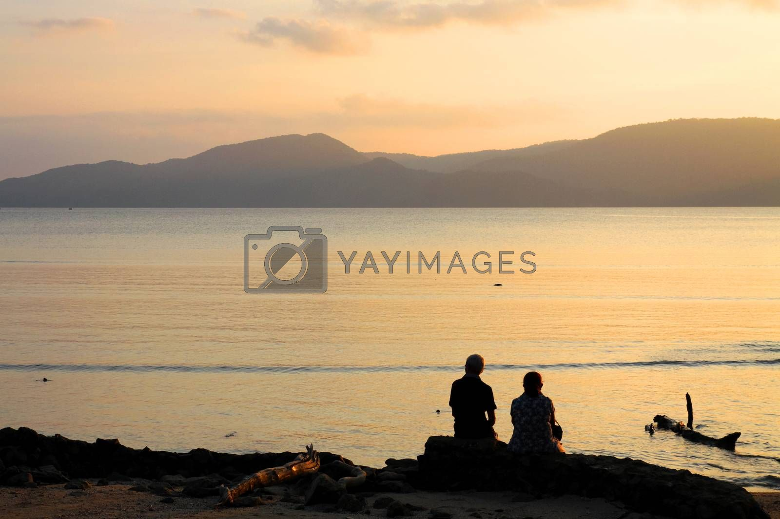Royalty free image of Port Blair, Andamans, India.28January2012. Silhouette Unknown Indian Couple enjoying sunset behind mountains of andaman sea by giddavr
