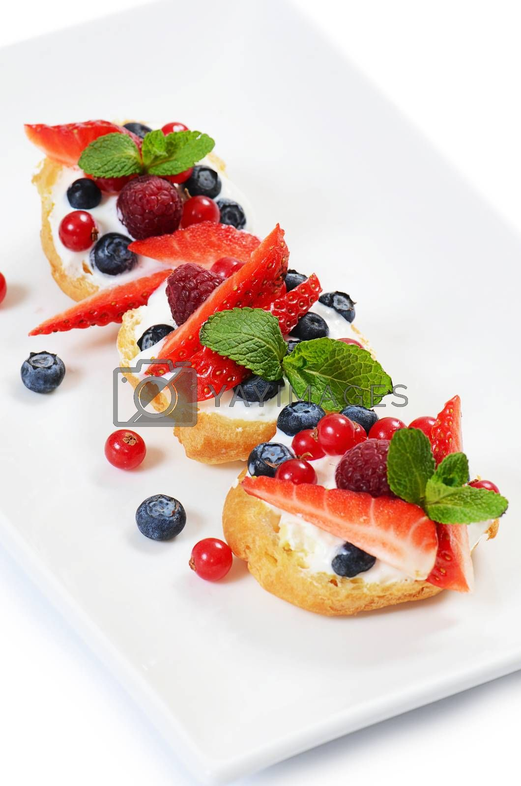 Royalty free image of Profiteroles with berries currant , strawberries by SvetaVo