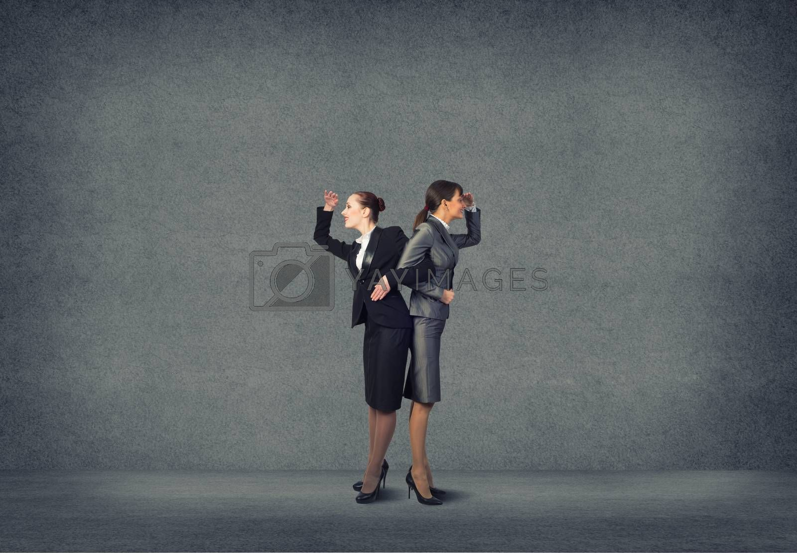 two business women holding hands, looking in different directions, teamwork