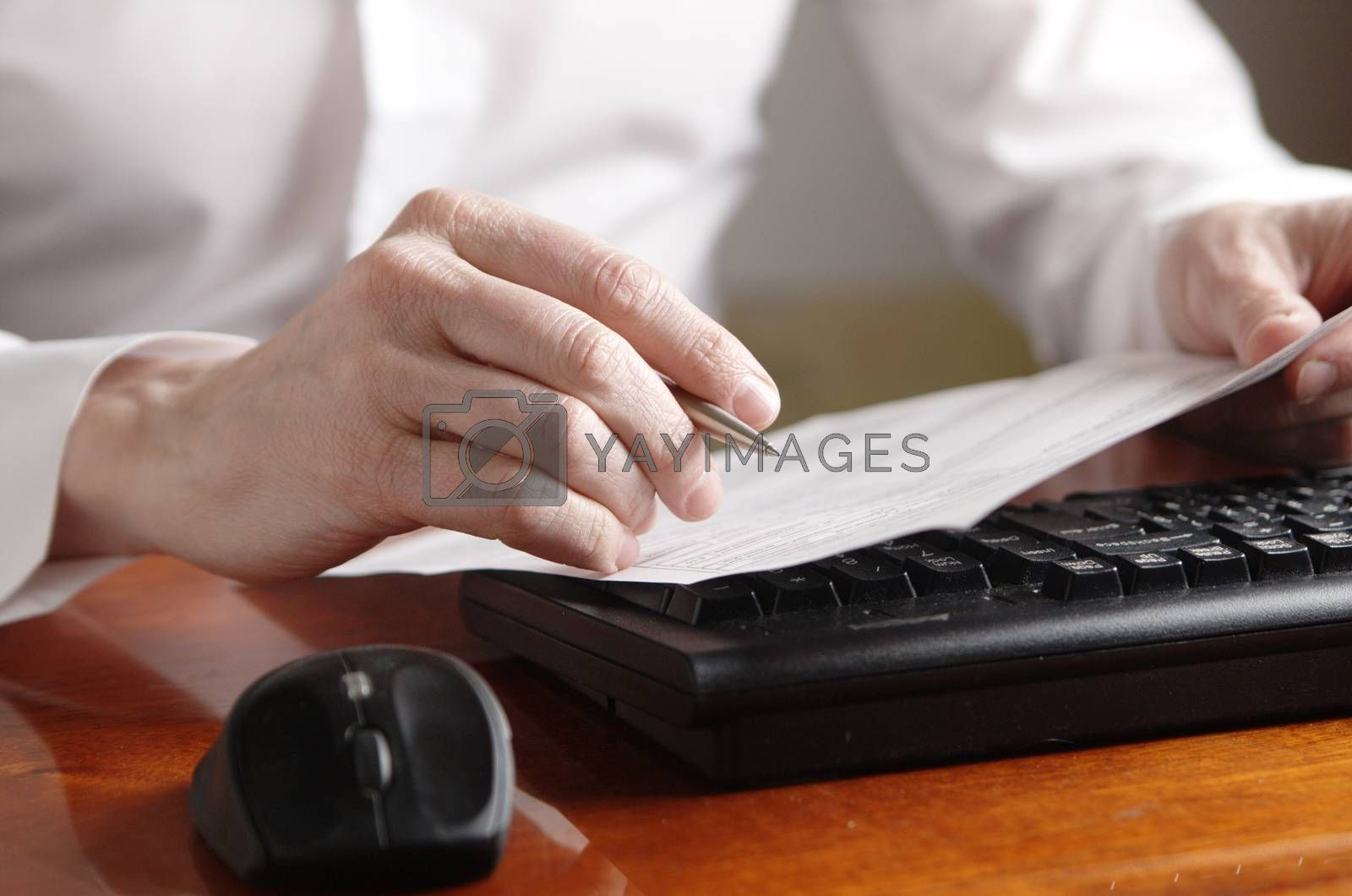 Royalty free image of Hands with document and pen on a computer keyboard by Ravenestling