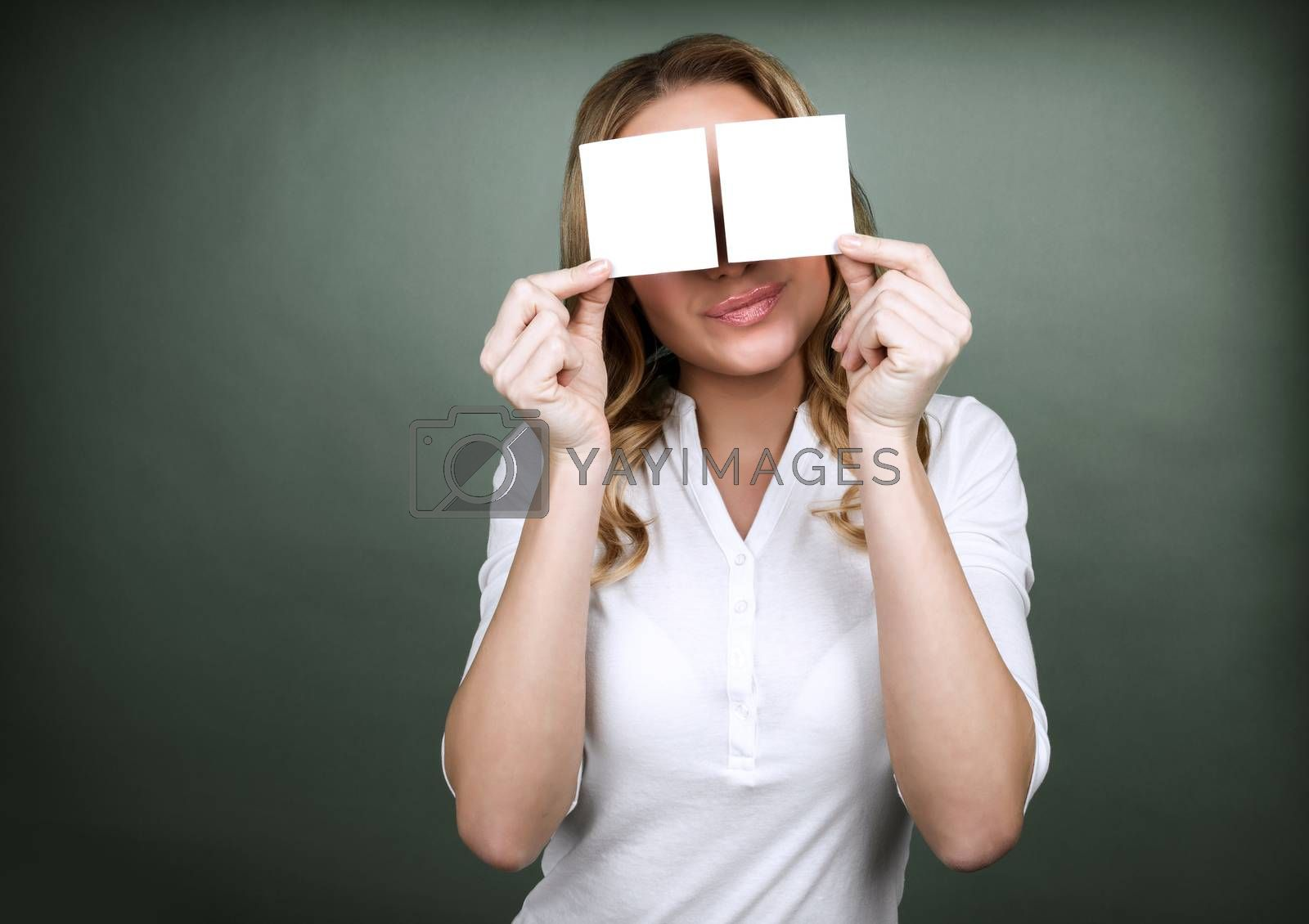 Portrait of young cute girl holding two blank card on her eyes isolated on grey background, copy space for information, advertisement concept