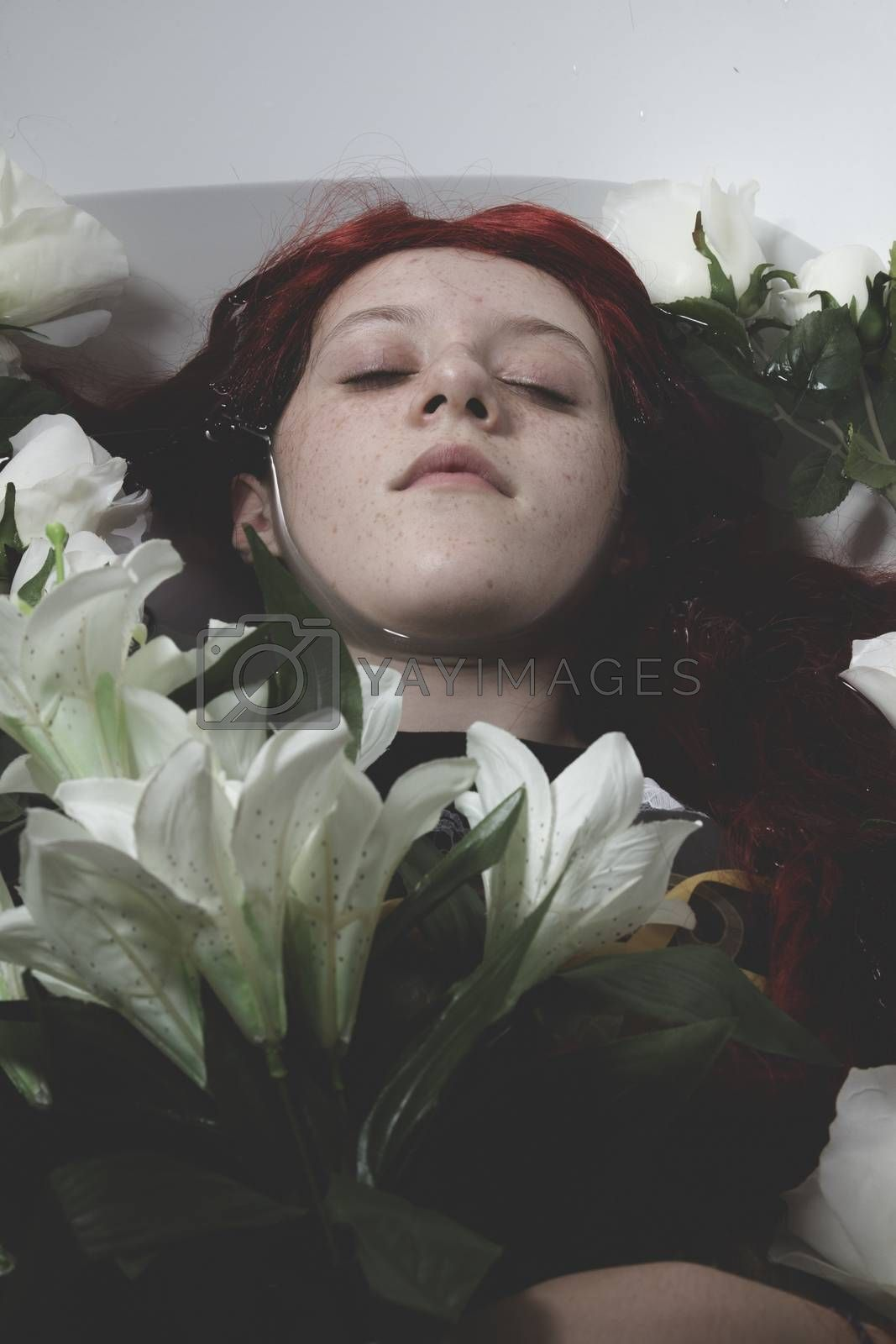 Fashion, Teen submerged in water with white roses, romance scene