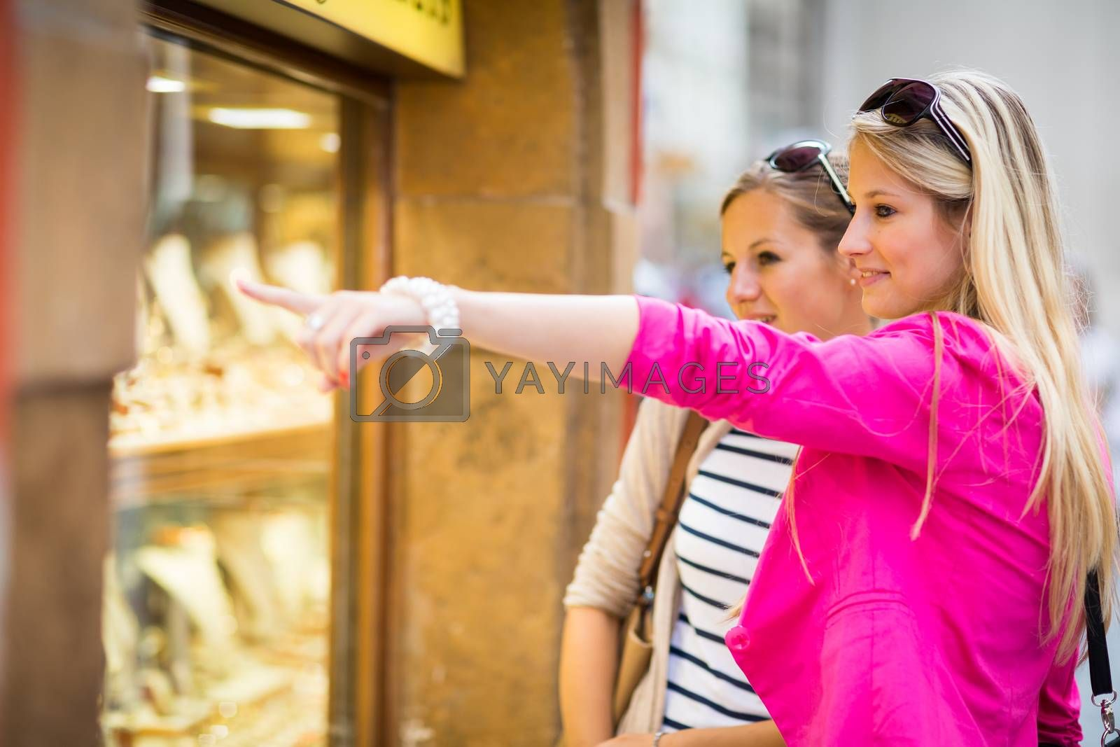Two pretty, young women window shopping in a city