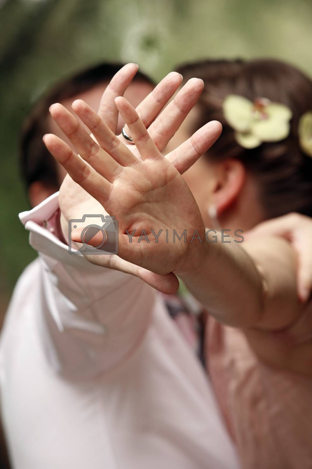 The groom is closed from the photographer by a hand