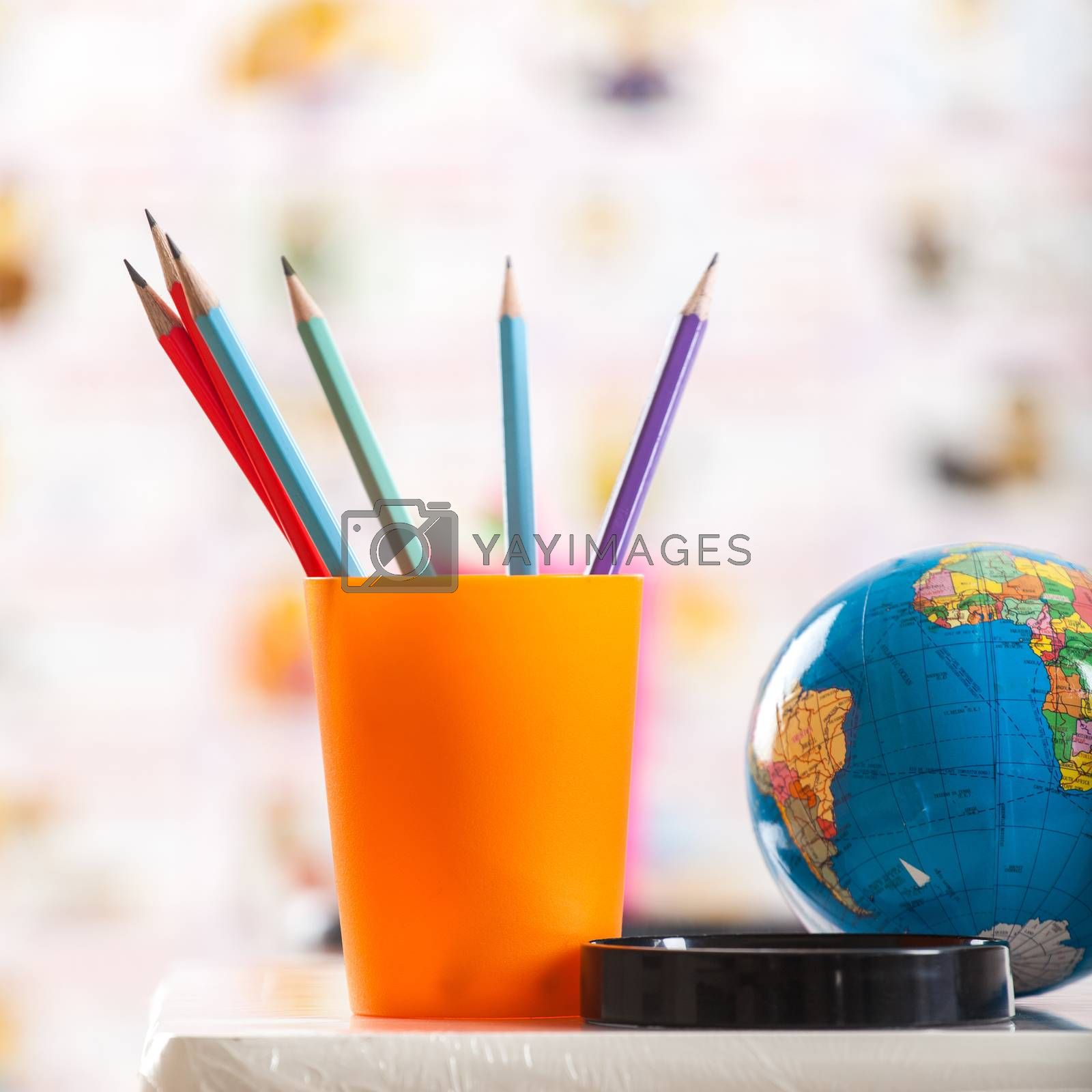 Pencils, globe and book on table