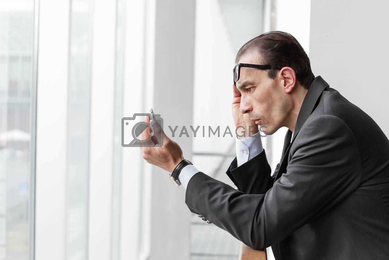 Poor eyesight Businessman trying to watch his phone display