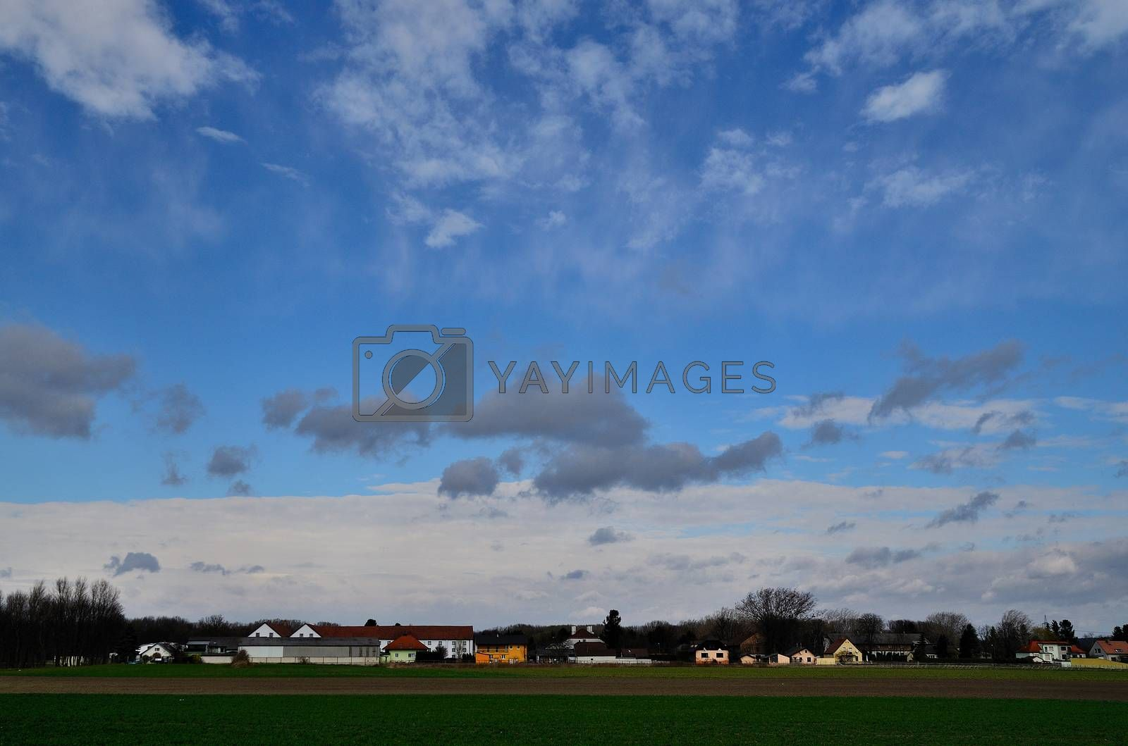 gray clouds on blue sky and colorful houses