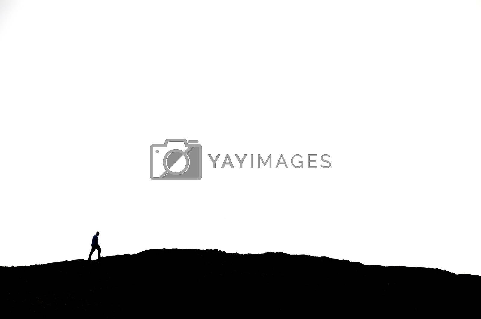 man on black mountain with white background