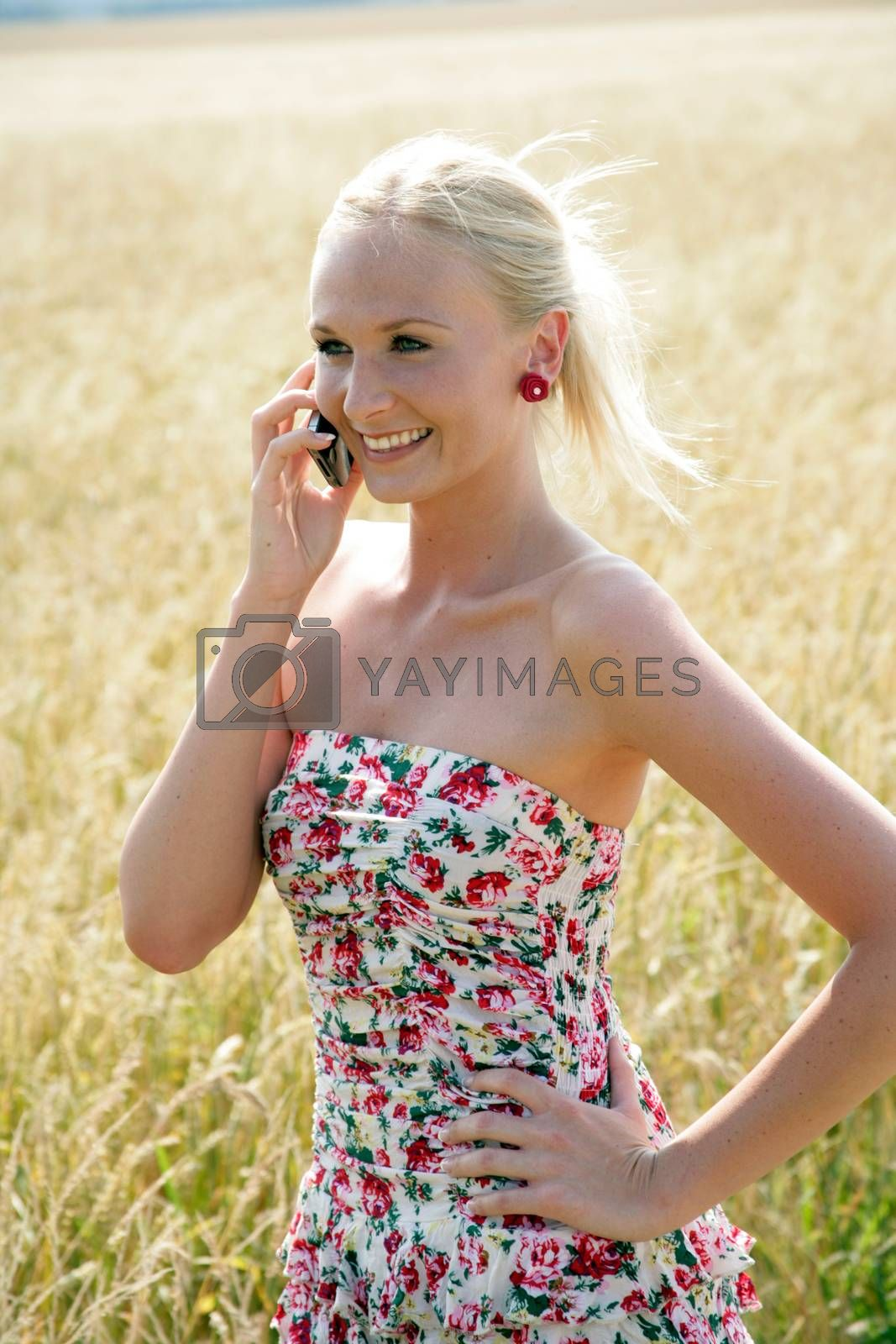 Young attractive woman is standing in a wheat field and speaks into her mobile phone. She looks happy and relaxed.