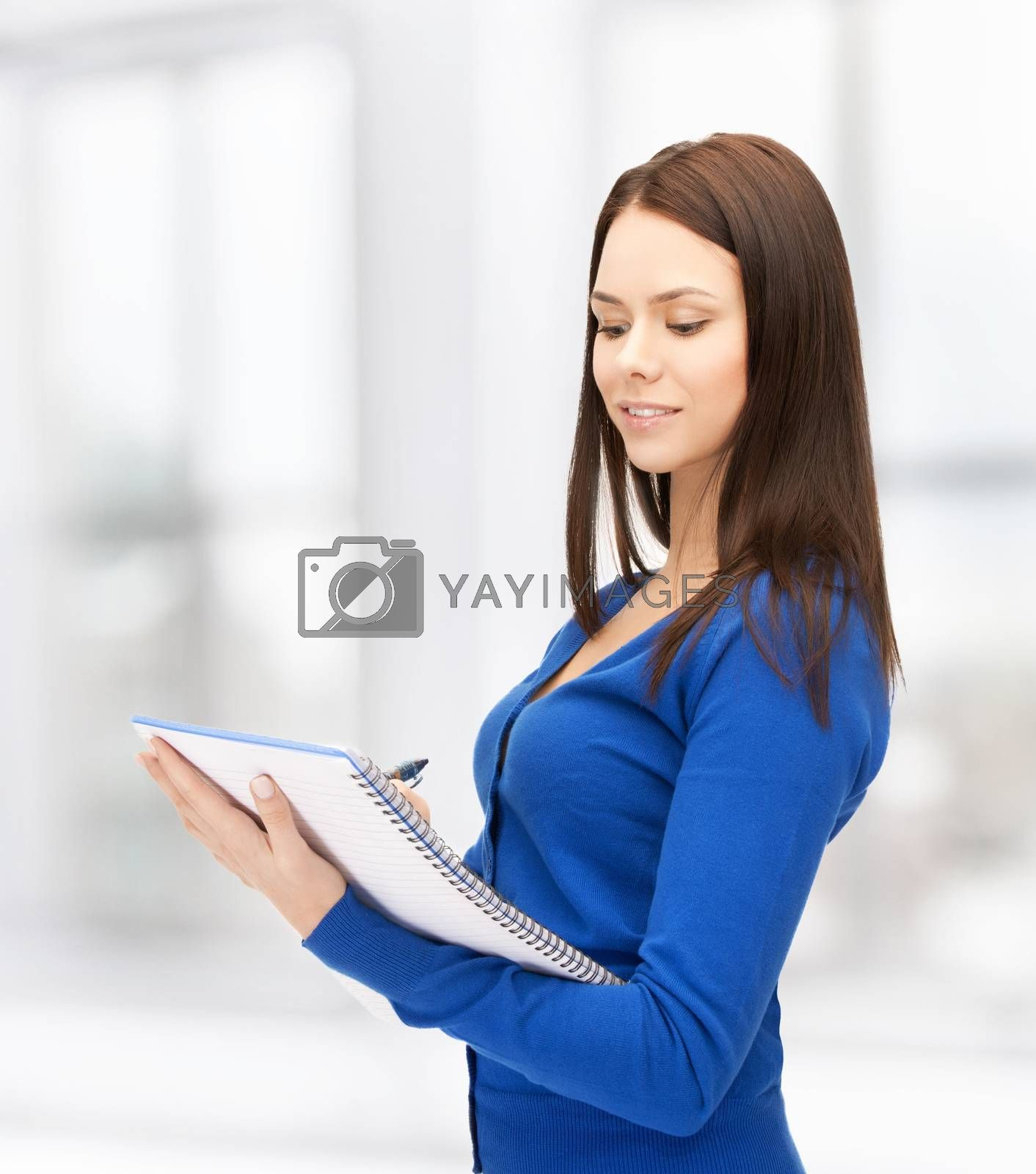 smiling young businesswoman with notebook by dolgachov