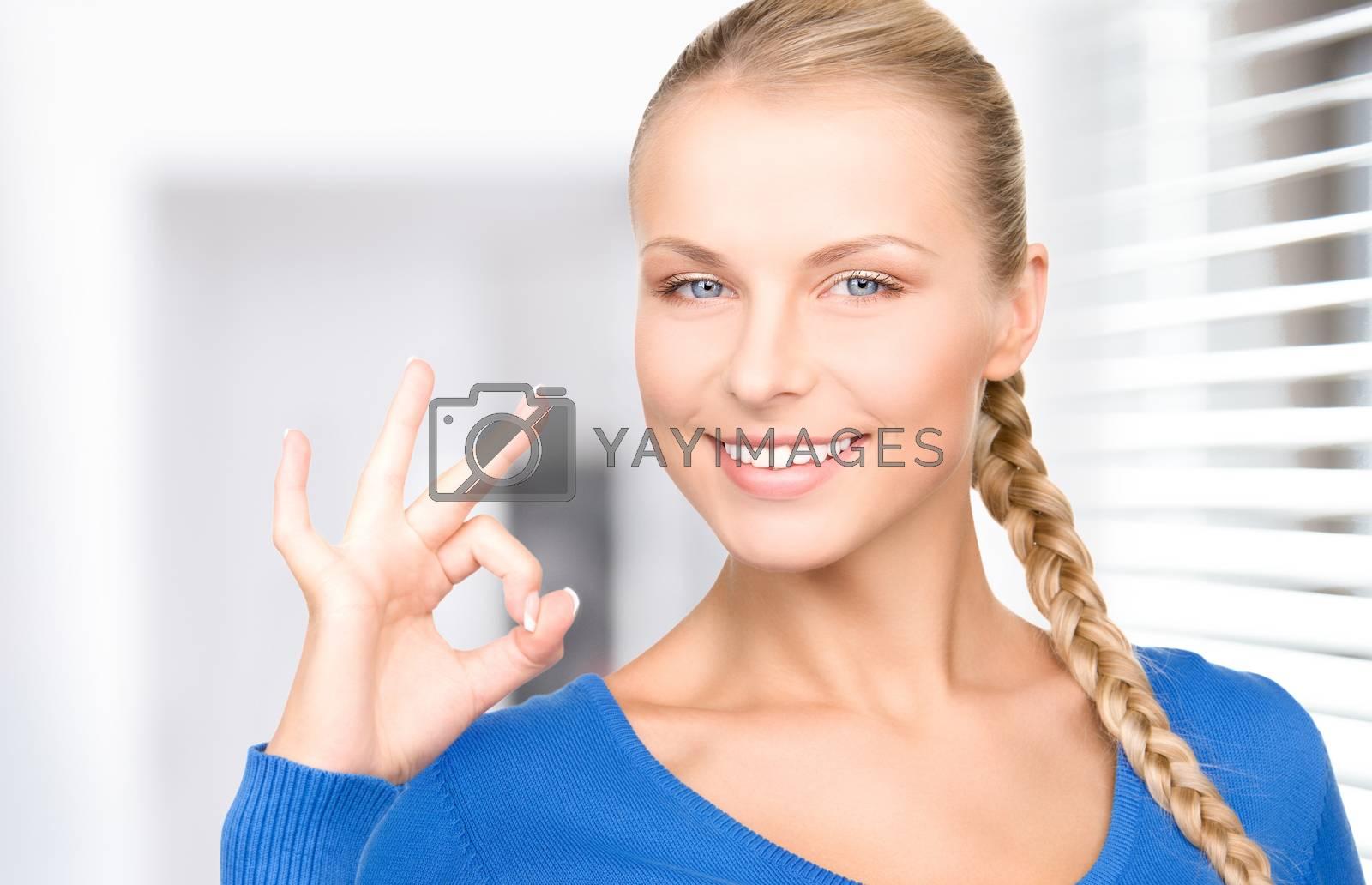 woman showing ok sign by dolgachov