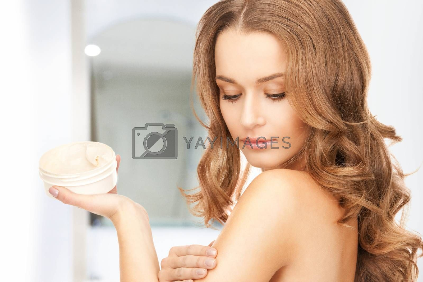 beautiful woman with moisturizing creme by dolgachov