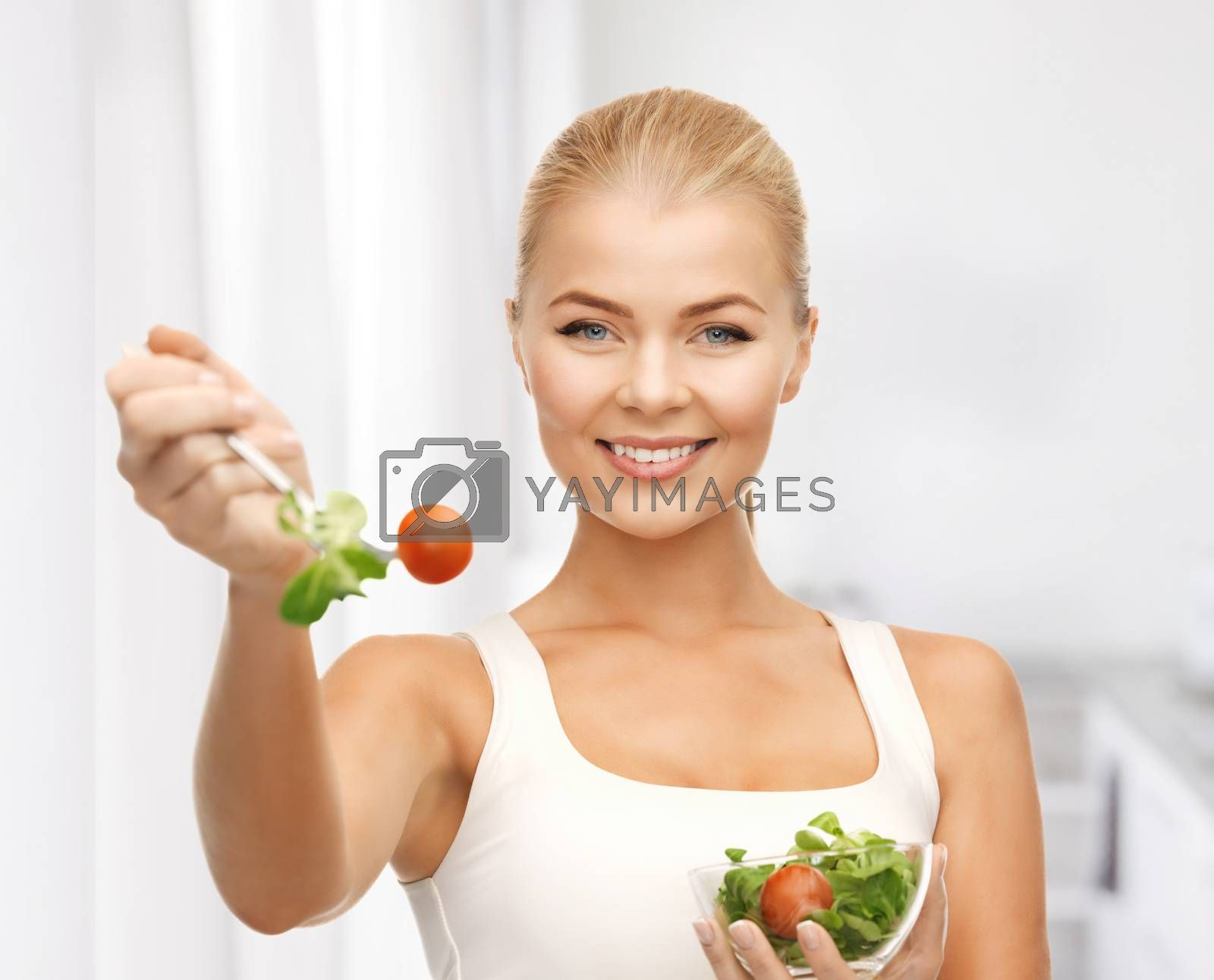 healthy woman holding bowl with salad by dolgachov