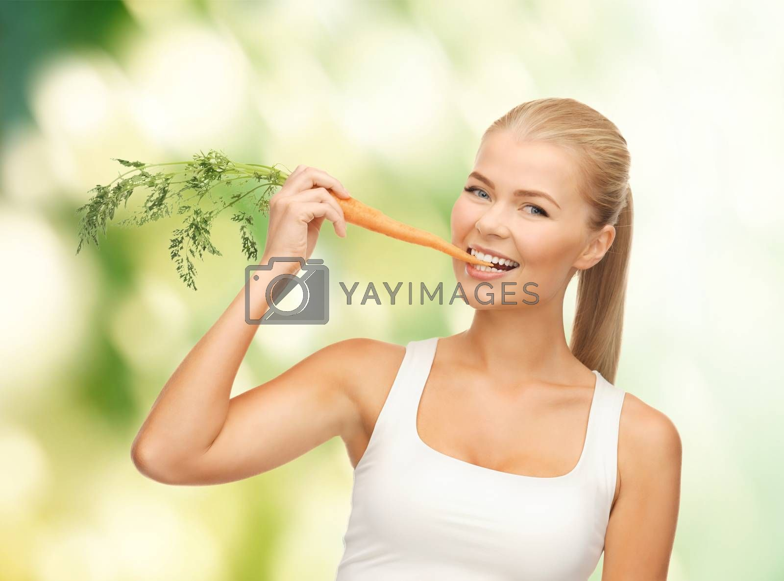 healthy young woman biting carrot by dolgachov