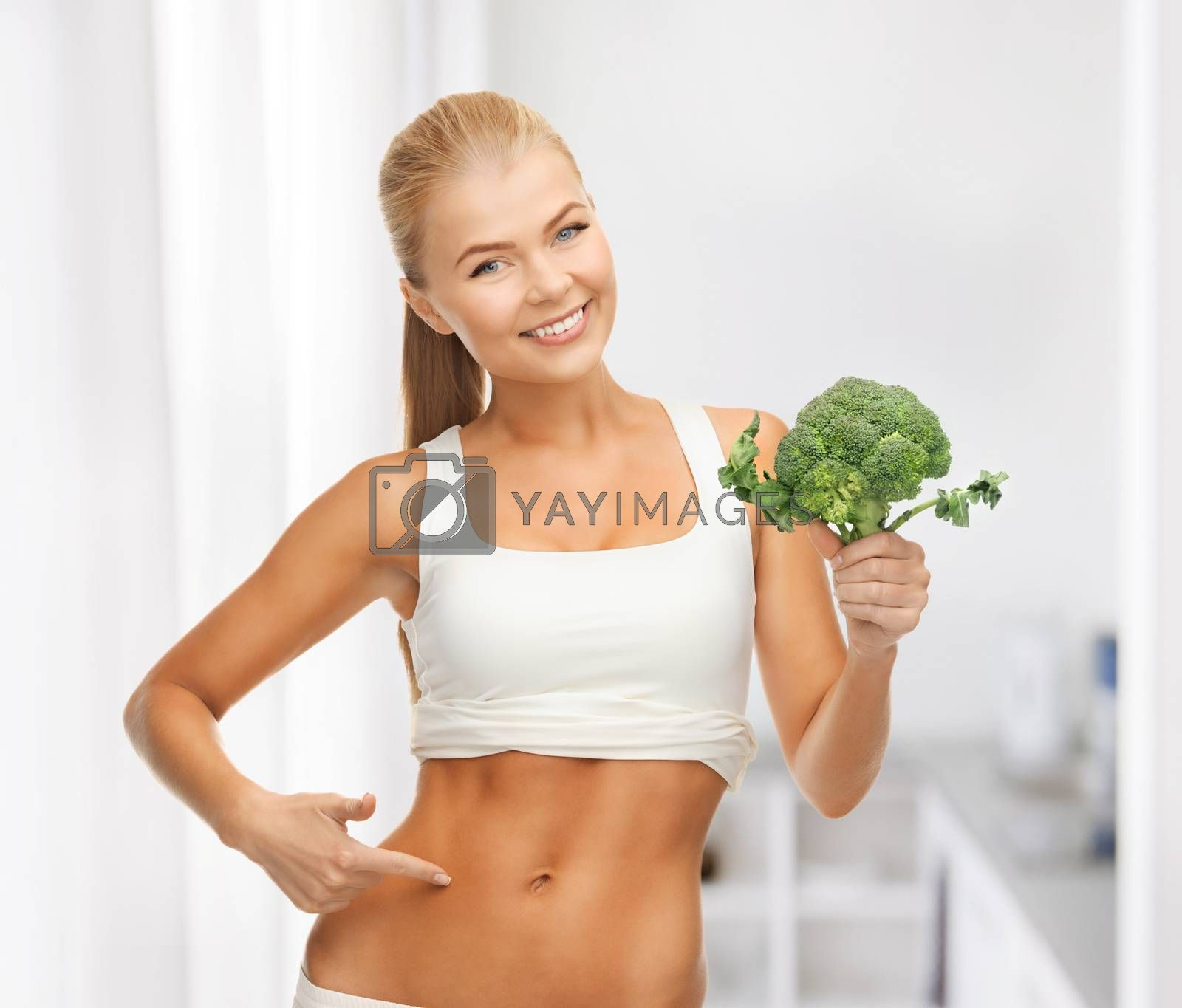 woman pointing at her abs and holding broccoli by dolgachov