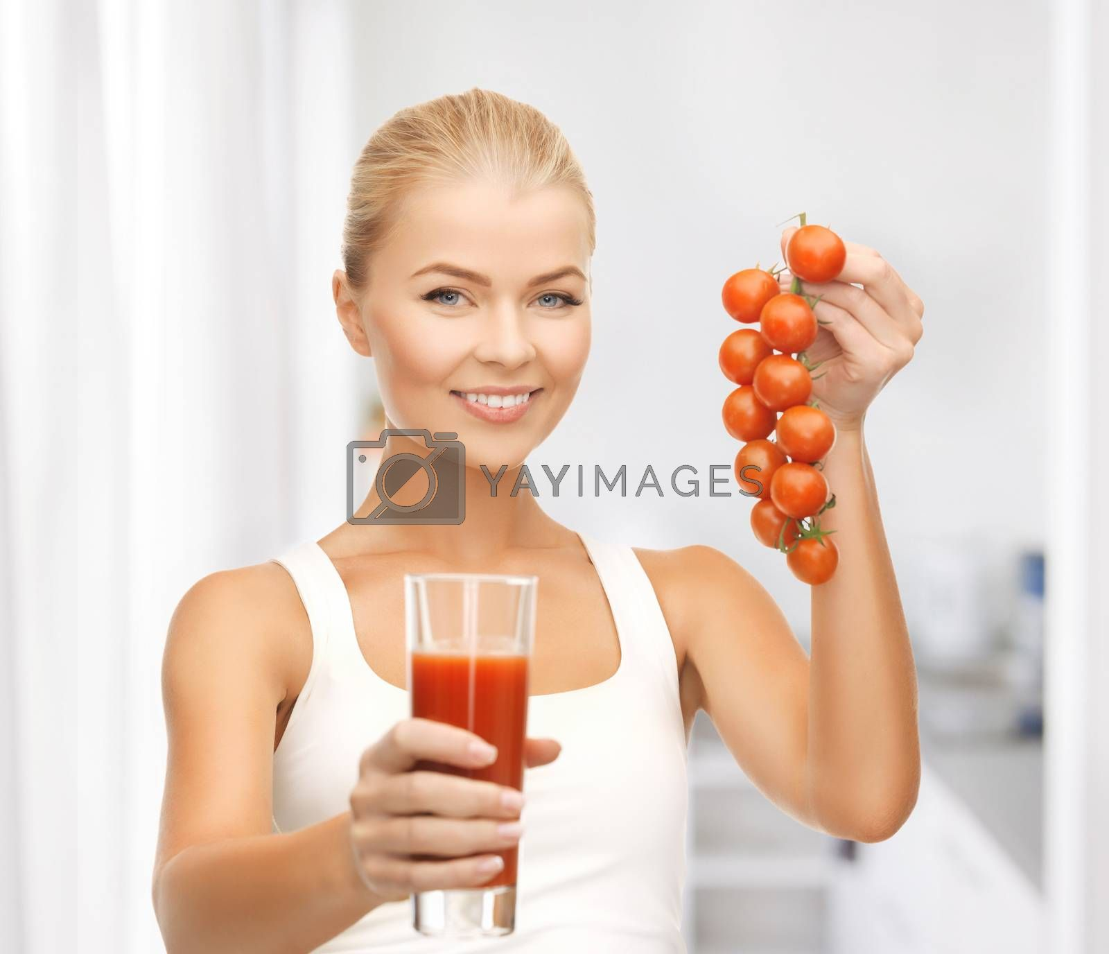 woman holding glass of juice and tomatoes by dolgachov