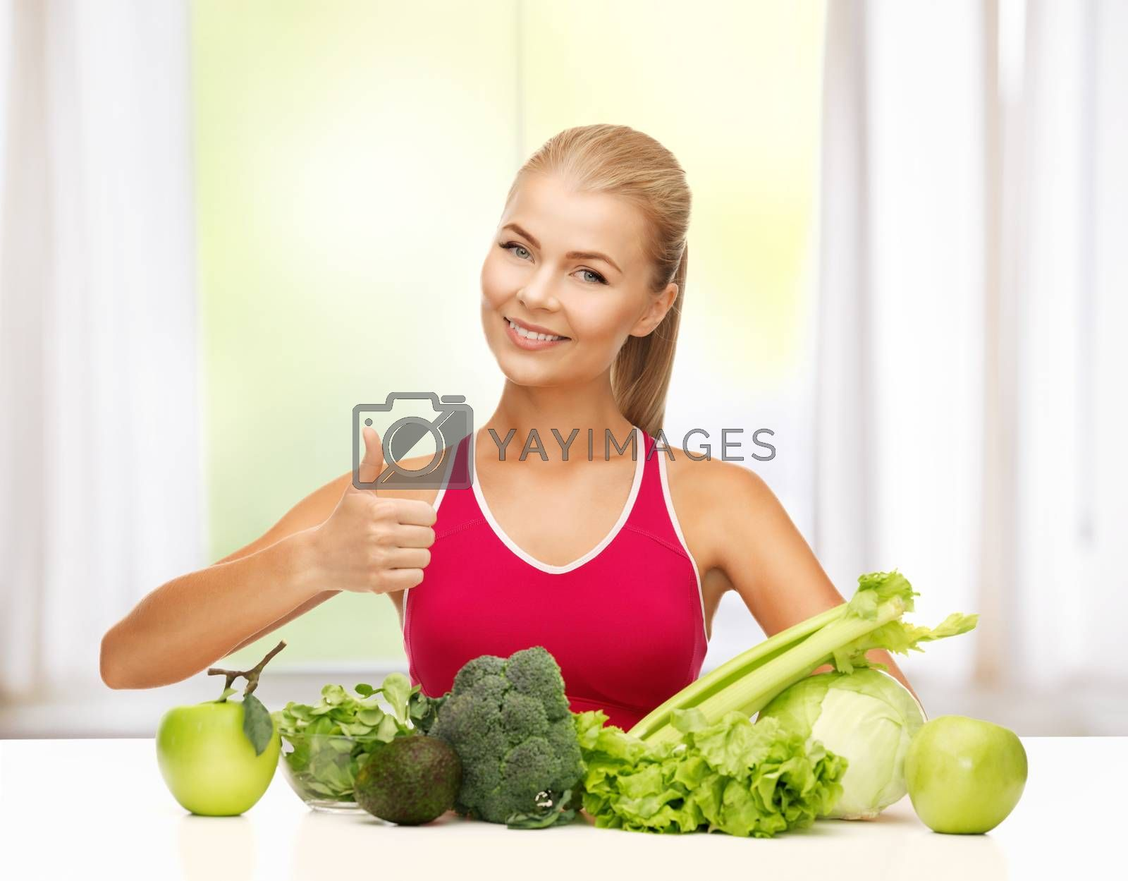 woman shows thumbs up with organic food by dolgachov