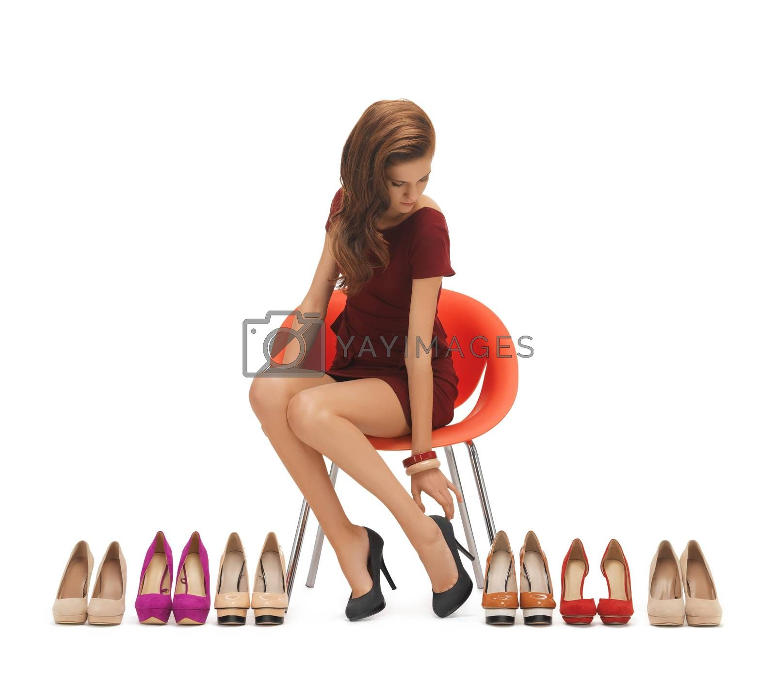 woman trying on high heeled shoes by dolgachov
