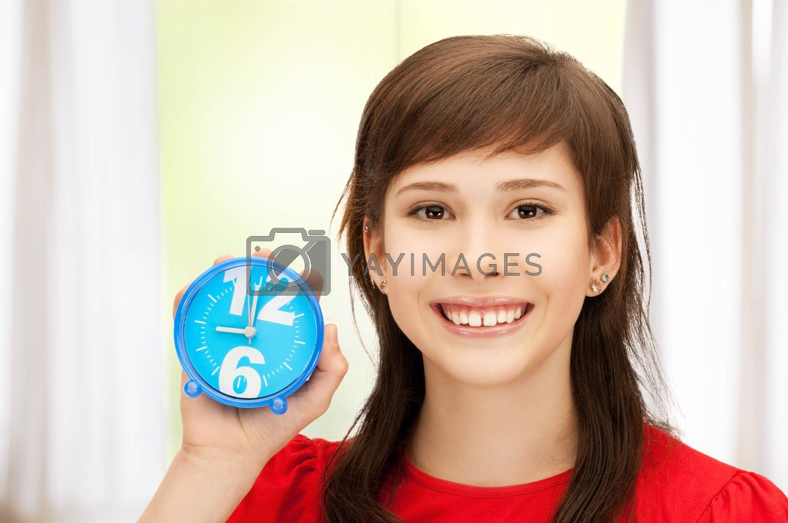 teenage girl holding alarm clock by dolgachov