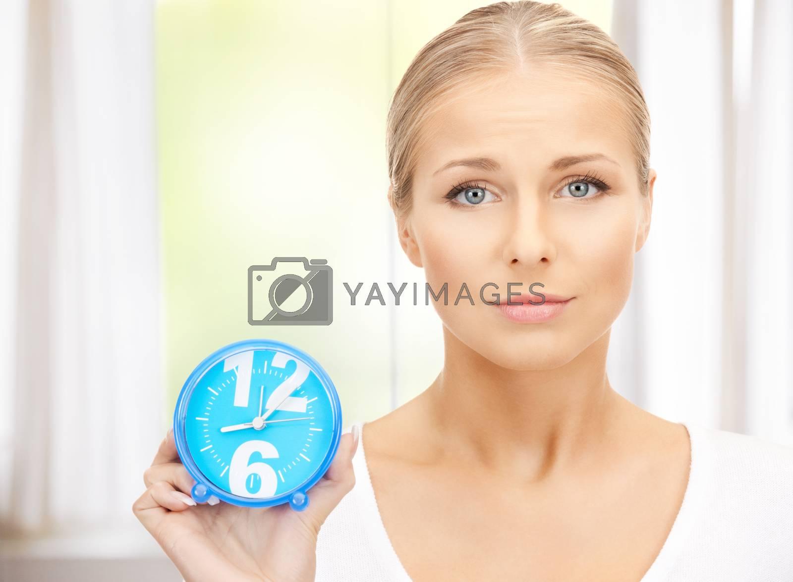 woman holding alarm clock by dolgachov