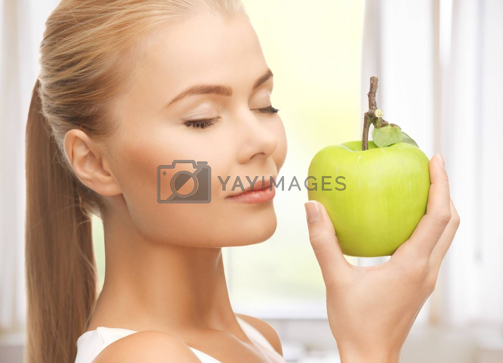 woman smelling apple by dolgachov
