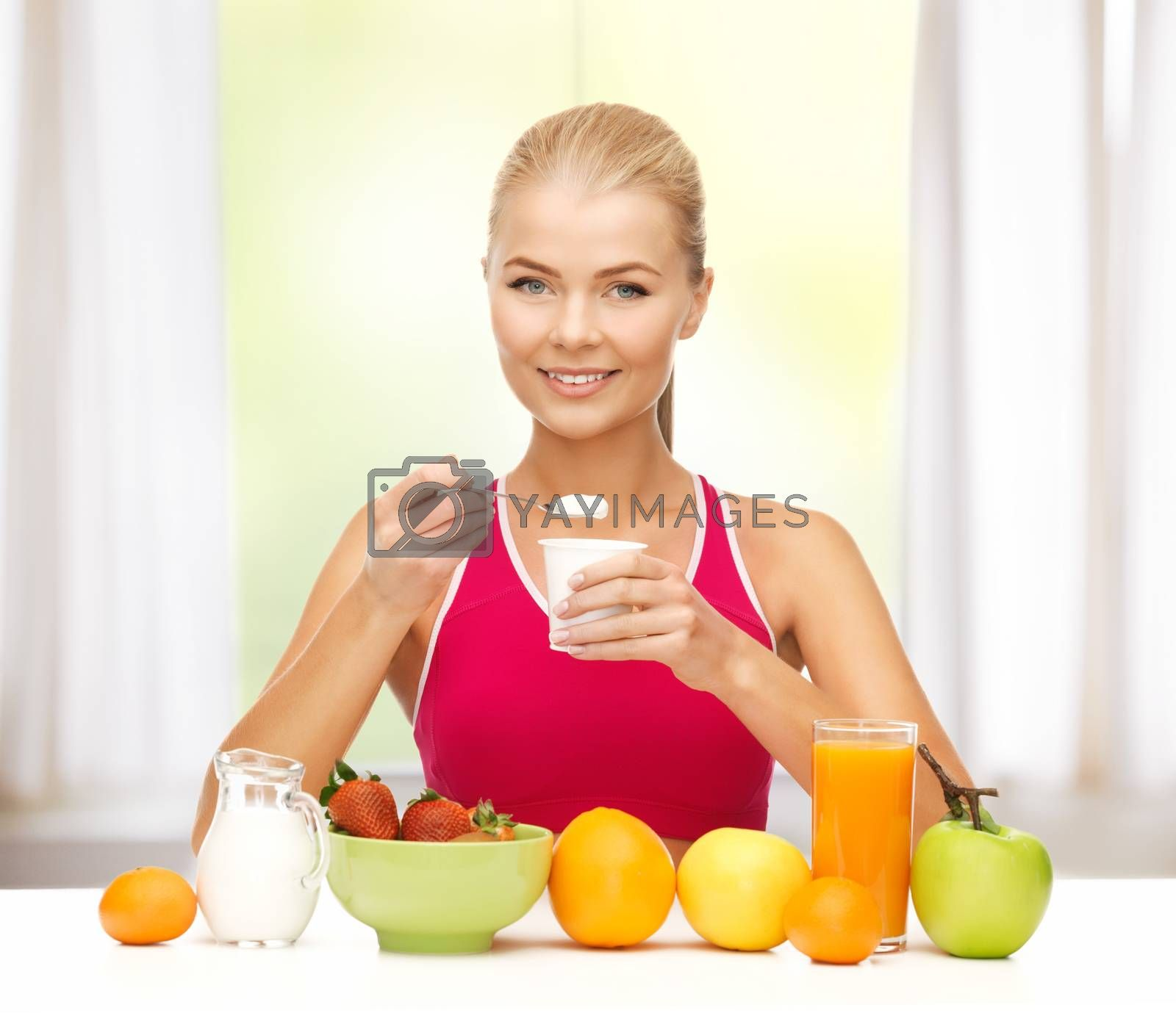 young woman eating healthy breakfast by dolgachov