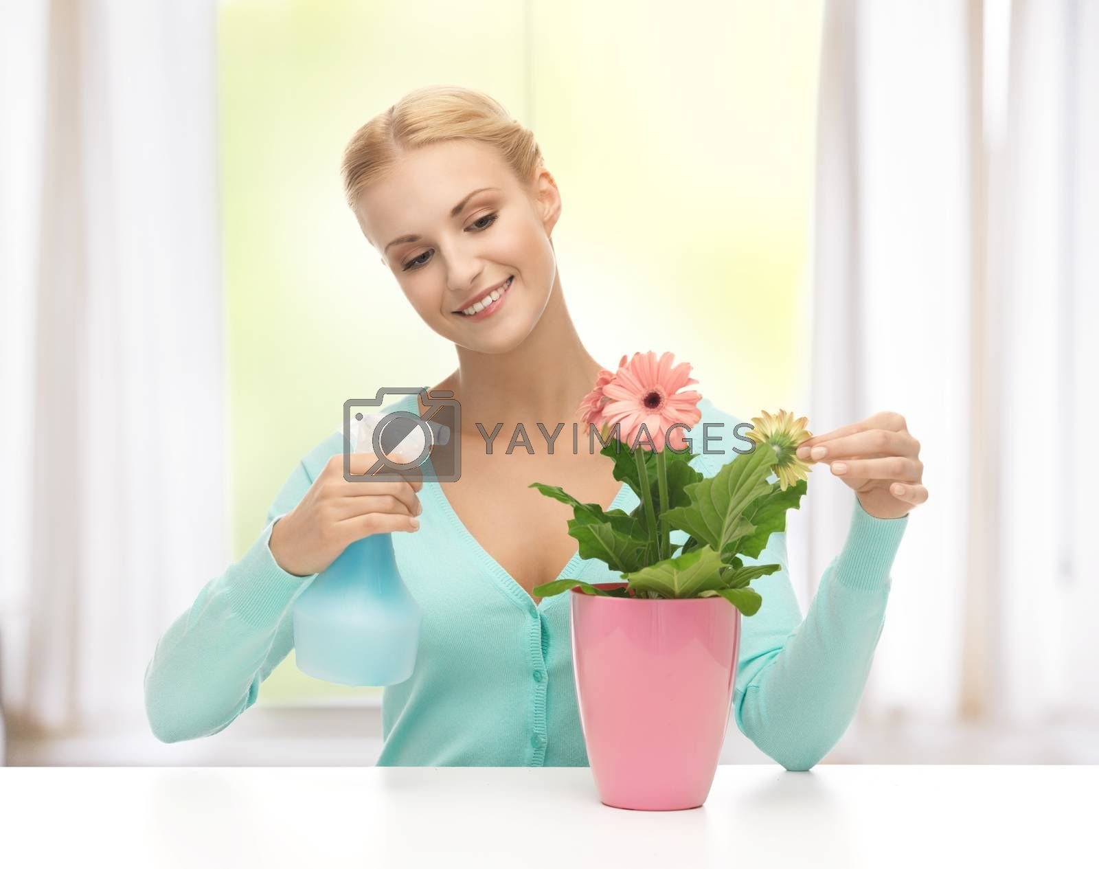 woman holding pot with flower and spray bottle by dolgachov