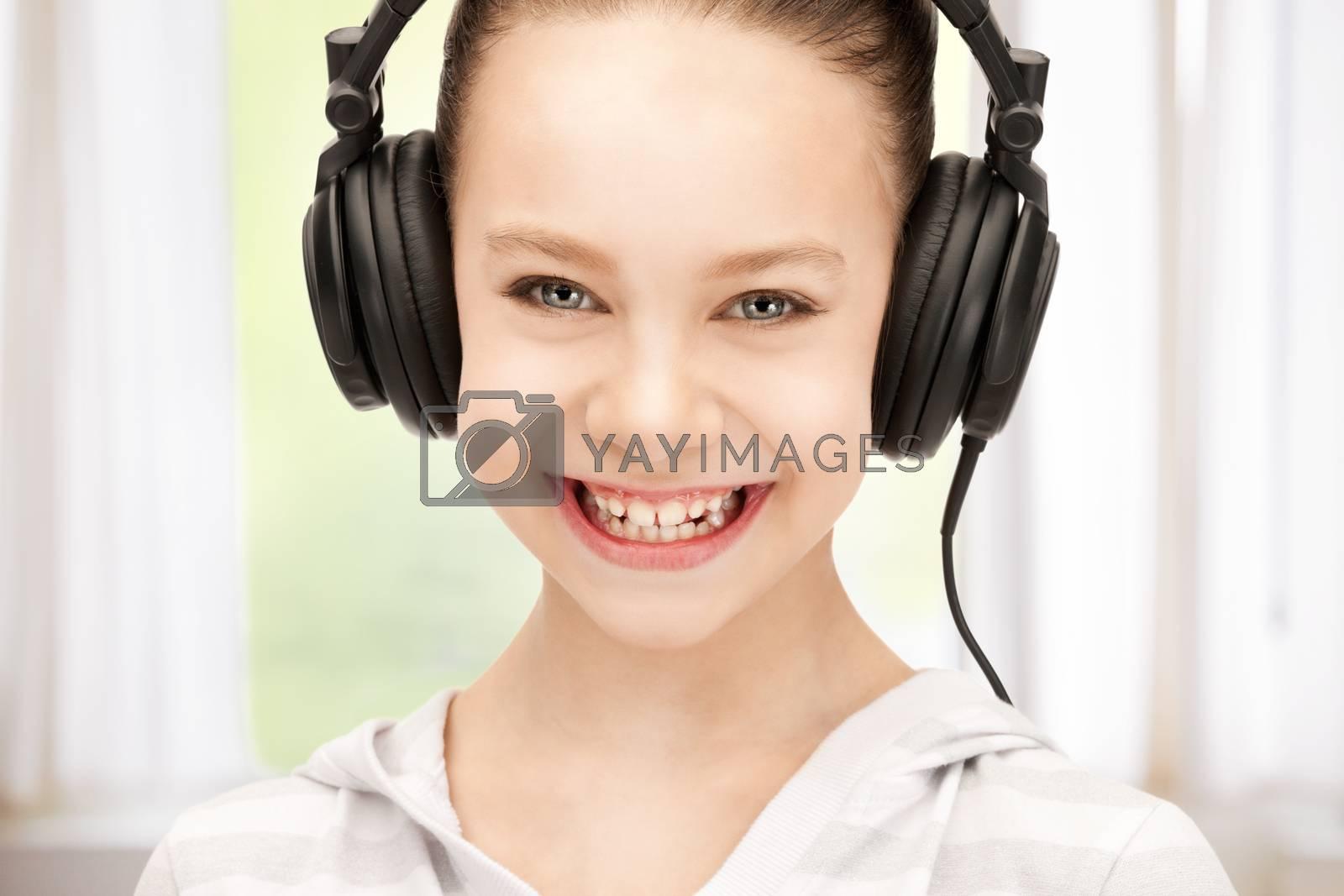 happy teenage girl in big headphones by dolgachov