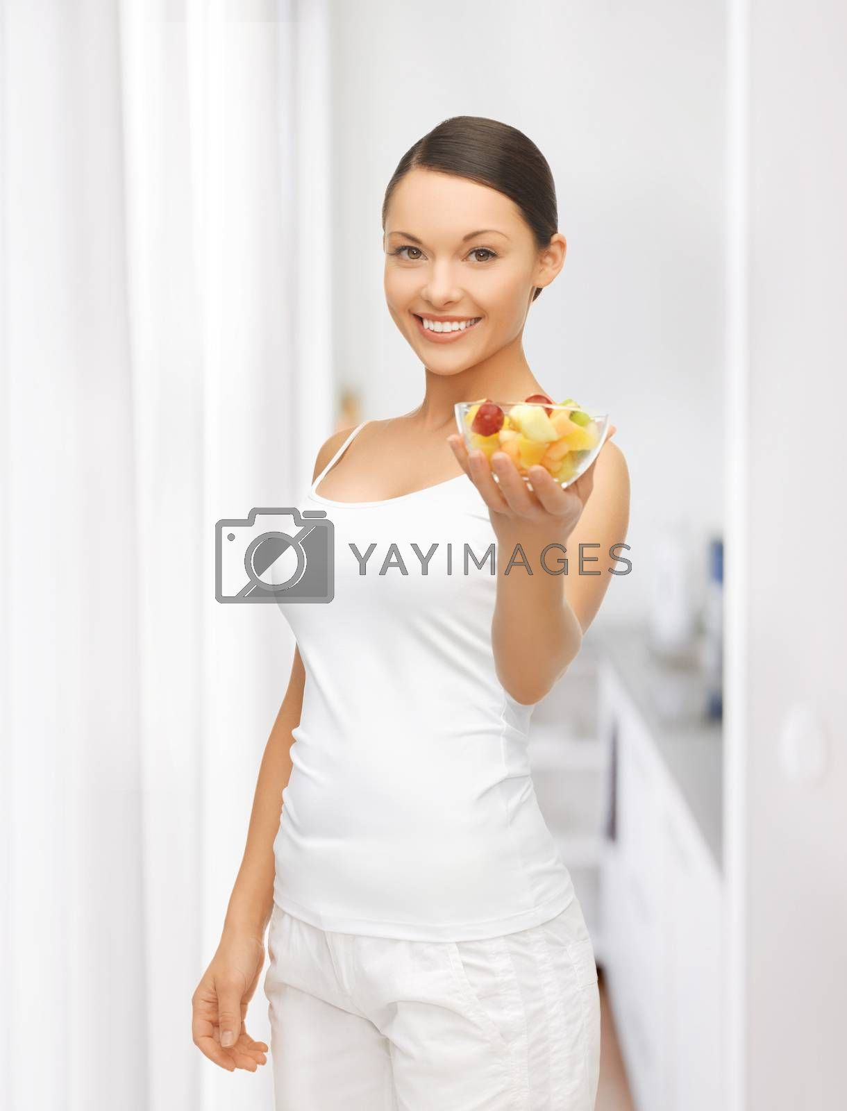 healthy woman holding bowl with fruit salad by dolgachov
