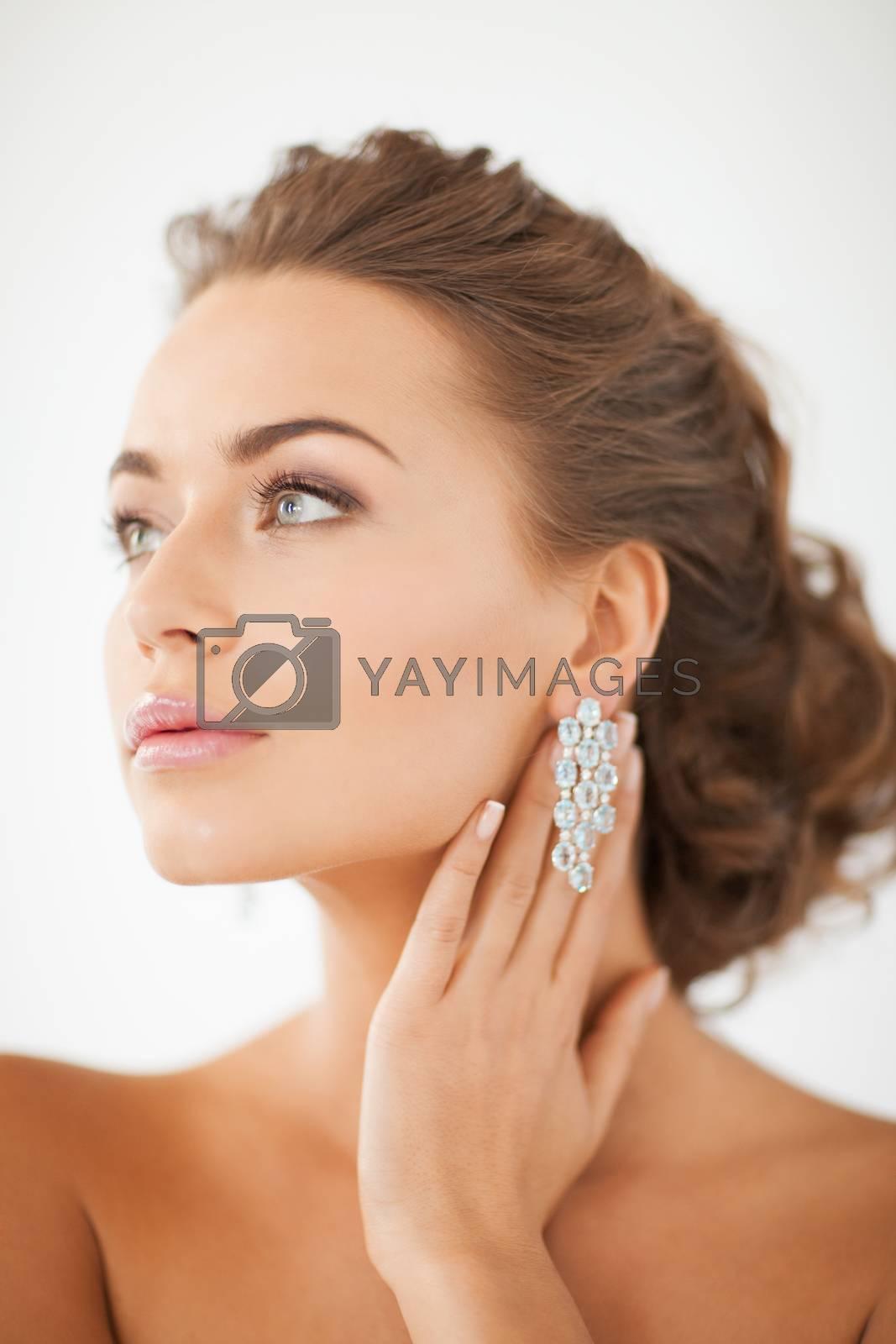 woman wearing shiny diamond earrings by dolgachov