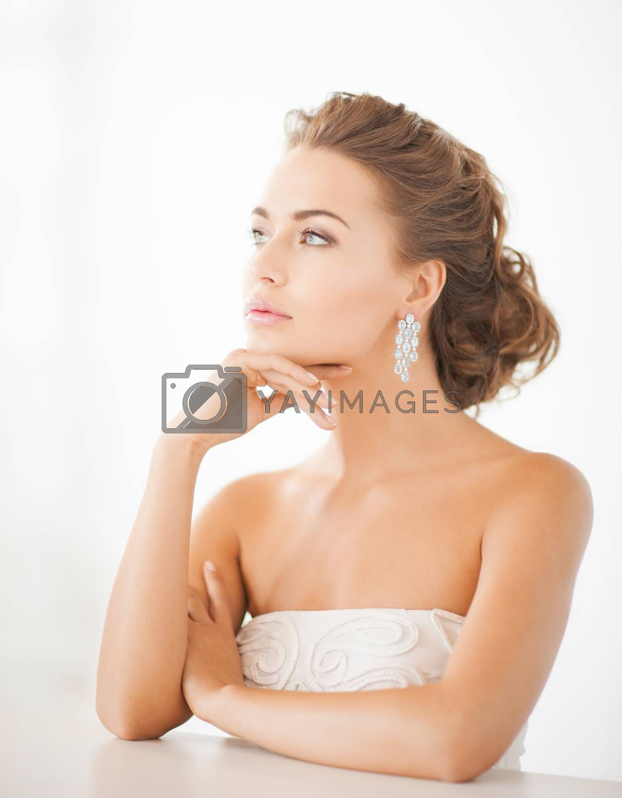 woman wearing shiny diamond earrings by dolgachov