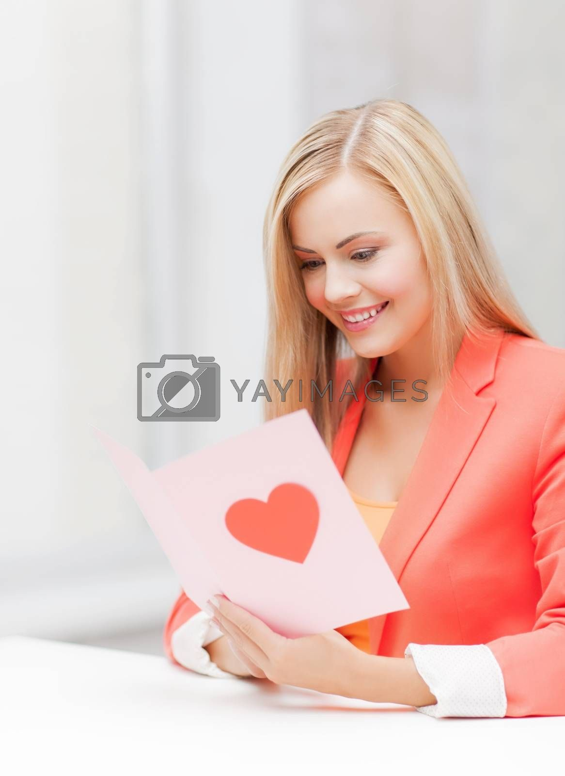 woman holding postcard with heart shape by dolgachov