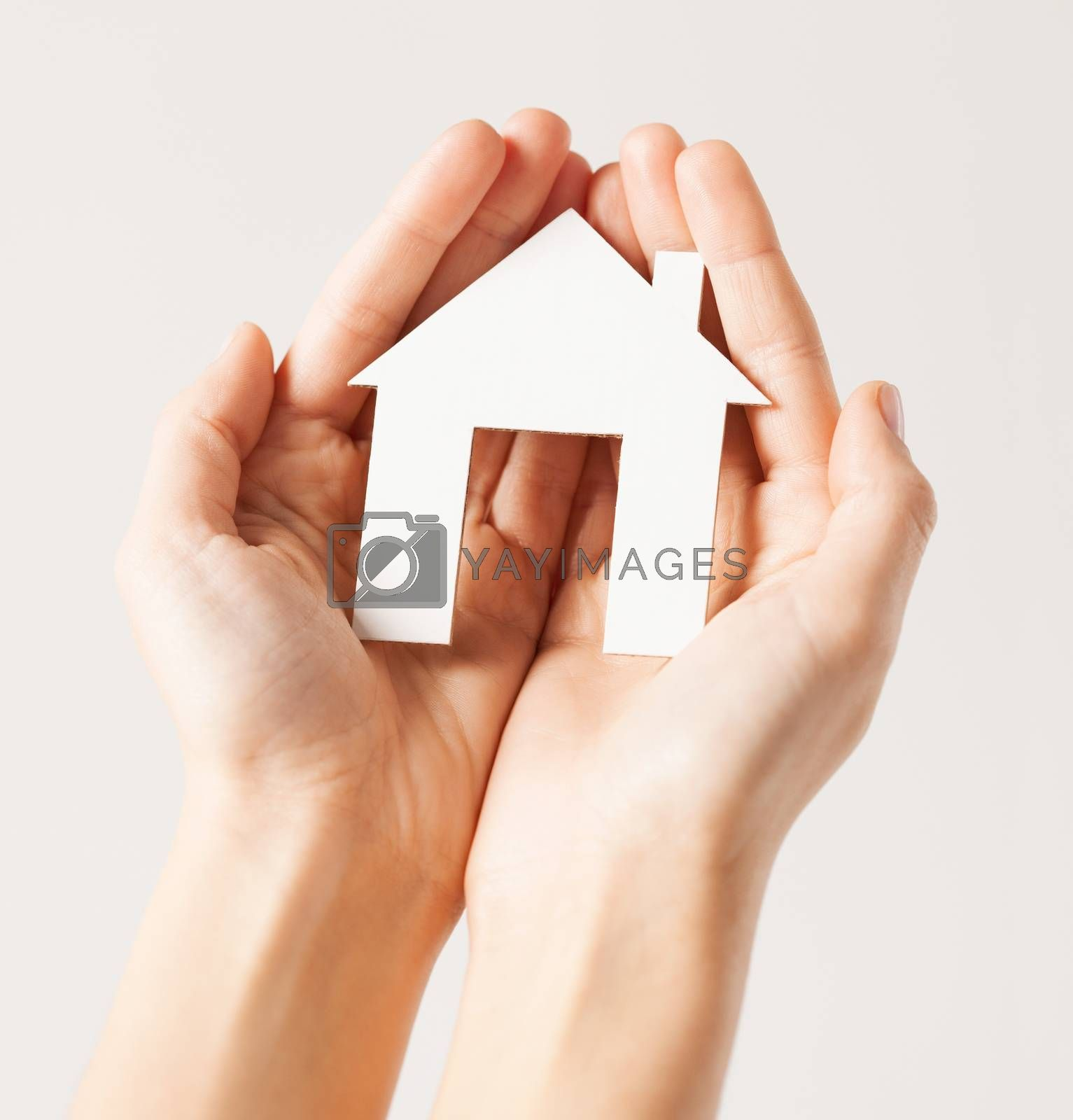 woman hands with paper house by dolgachov