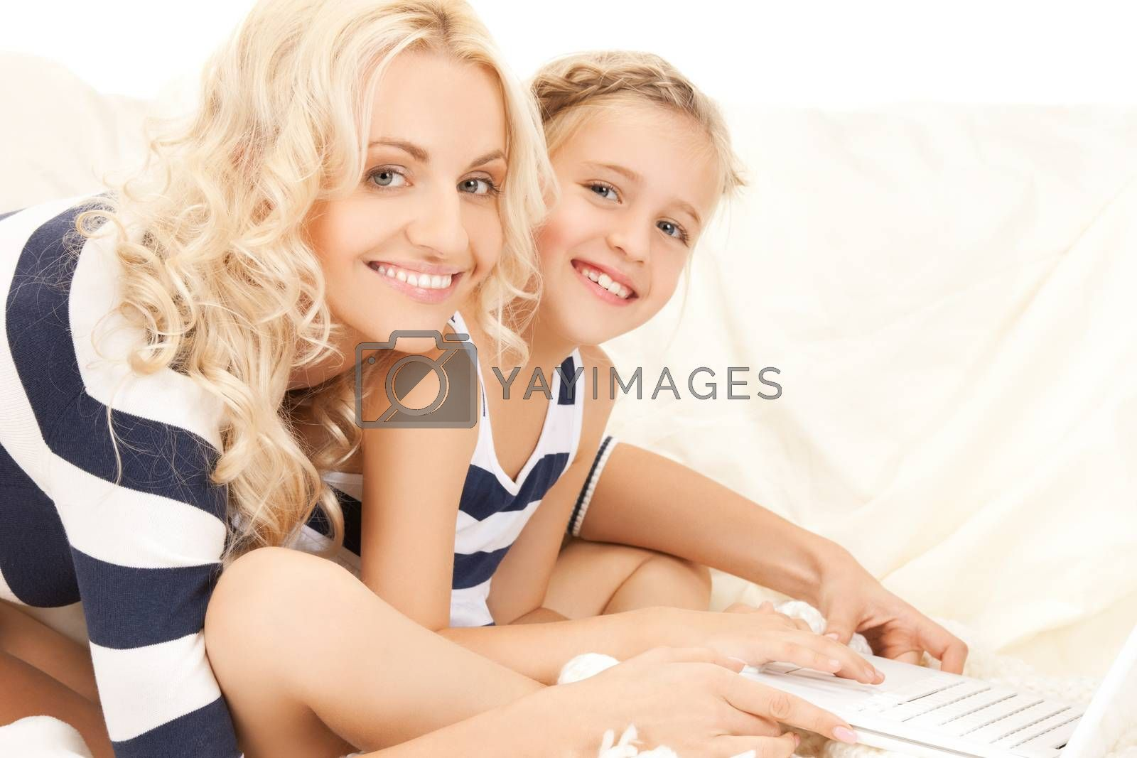 mother and daughter with laptop by dolgachov